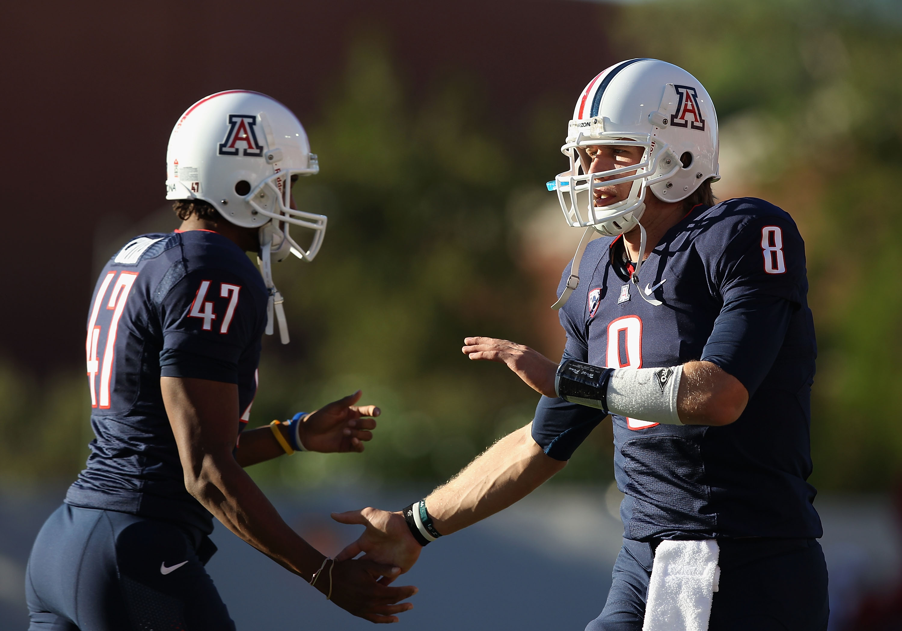 TUCSON, AZ - OCTOBER 09:  Quarterback Nick Foles #8 of the Arizona Wildcats celebrates with teammate Keenyn Crier #47 after the Wildcats scored a first quarter touchdown against the Oregon State Beavers during the college football game at Arizona Stadium