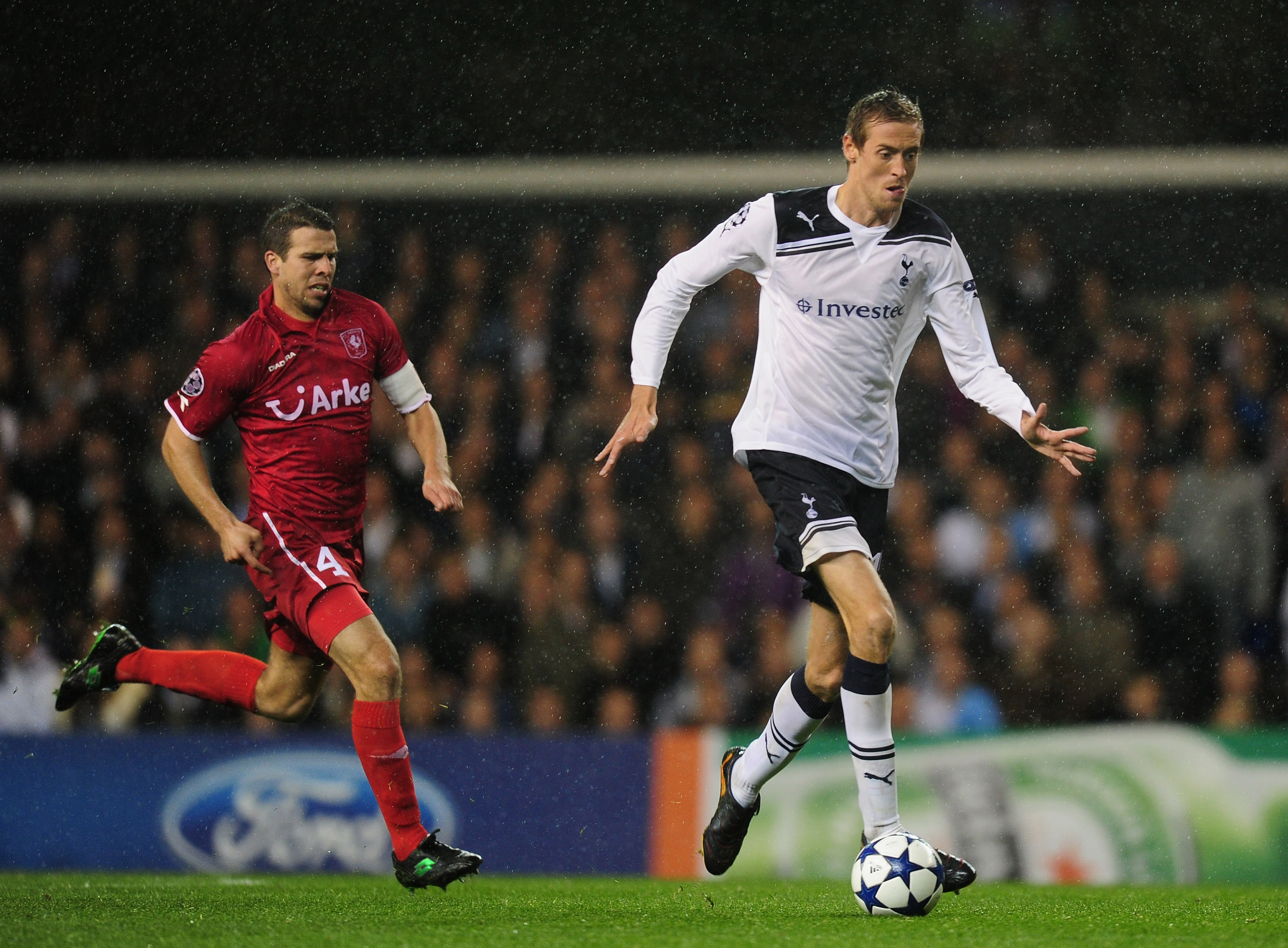 LONDON, ENGLAND - SEPTEMBER 29:  Peter Crouch of Tottenham is chased by Peter Wisgerhof of FC Twente looks on during the  UEFA Champions League Group A match between Tottenham Hotspur and FC Twente at White Hart Lane on September 29, 2010 in London, Engla