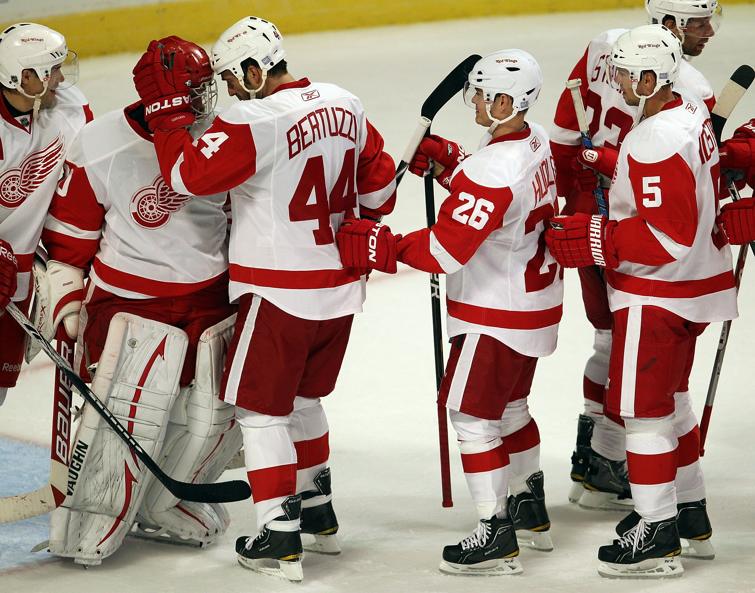 CHICAGO - OCTOBER 09: Chris Osgood #30 of the Detroit Red Wings is congratulated by teammates Todd Bertuzzi #44, Jiri Hudler #26 and Nicklas Lidstrom #5 after a win over the Chicago  Blackhawks at the United Center on October 9, 2010 in Chicago, Illinois.