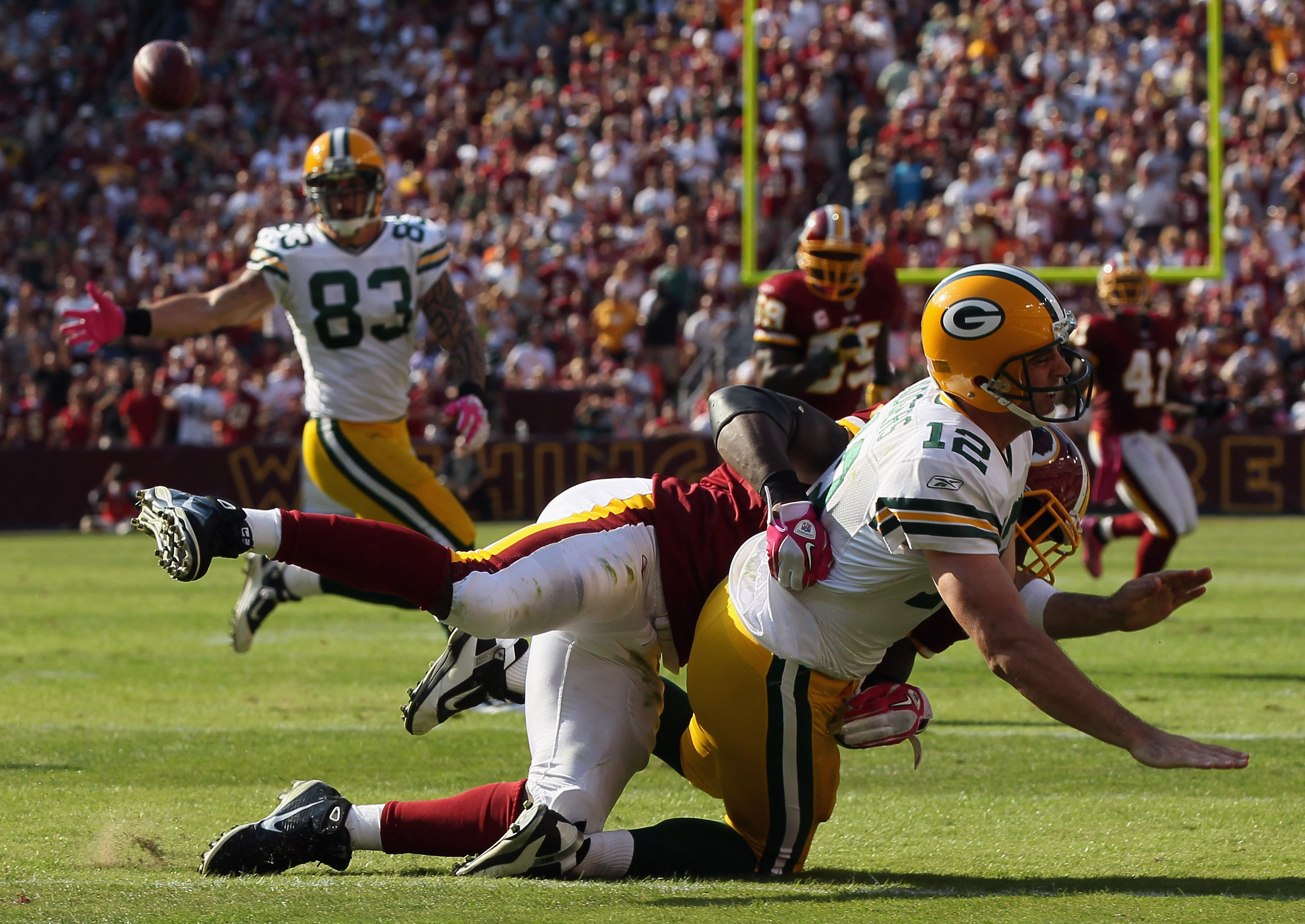 LANDOVER, MD - OCTOBER 10:  Quarterback Aaron Rodgers #12 of the Green Bay Packers is taken to the ground by lineback Brian Orakpo #98 of the Washington Redskins in the fourth quarter at FedExField on October 10, 2010 in Landover, Maryland. The Redskins w