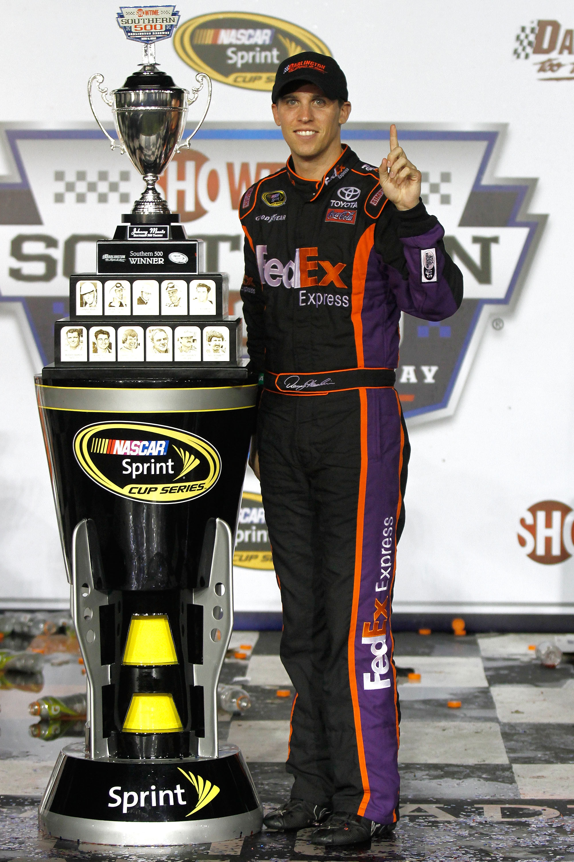 DARLINGTON, SC - MAY 08:  Denny Hamlin, driver of the #11 FedEx Express Toyota, celebrates with the trophy in victory lane in celebration of winning the NASCAR Sprint Cup series SHOWTIME Southern 500 at Darlington Raceway on May 8, 2010 in Darlington, Sou