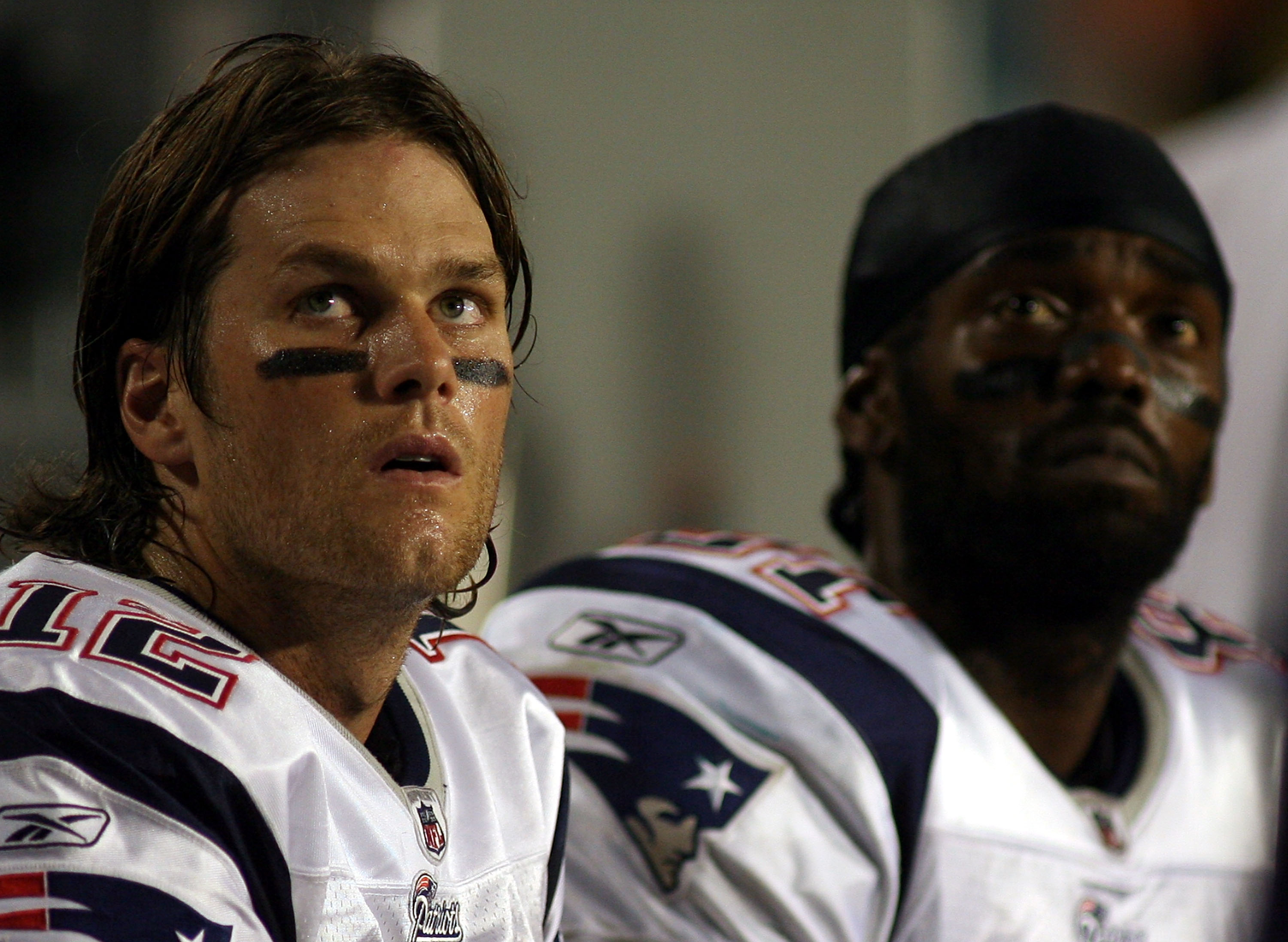 MIAMI - OCTOBER 04:  Quarterback Tom Brady #12 and Randy Moss of the New England Patriots sit on the sidelines  against the Miami Dolphins at Sun Life Stadium on October 4, 2010 in Miami, Florida.  (Photo by Marc Serota/Getty Images)