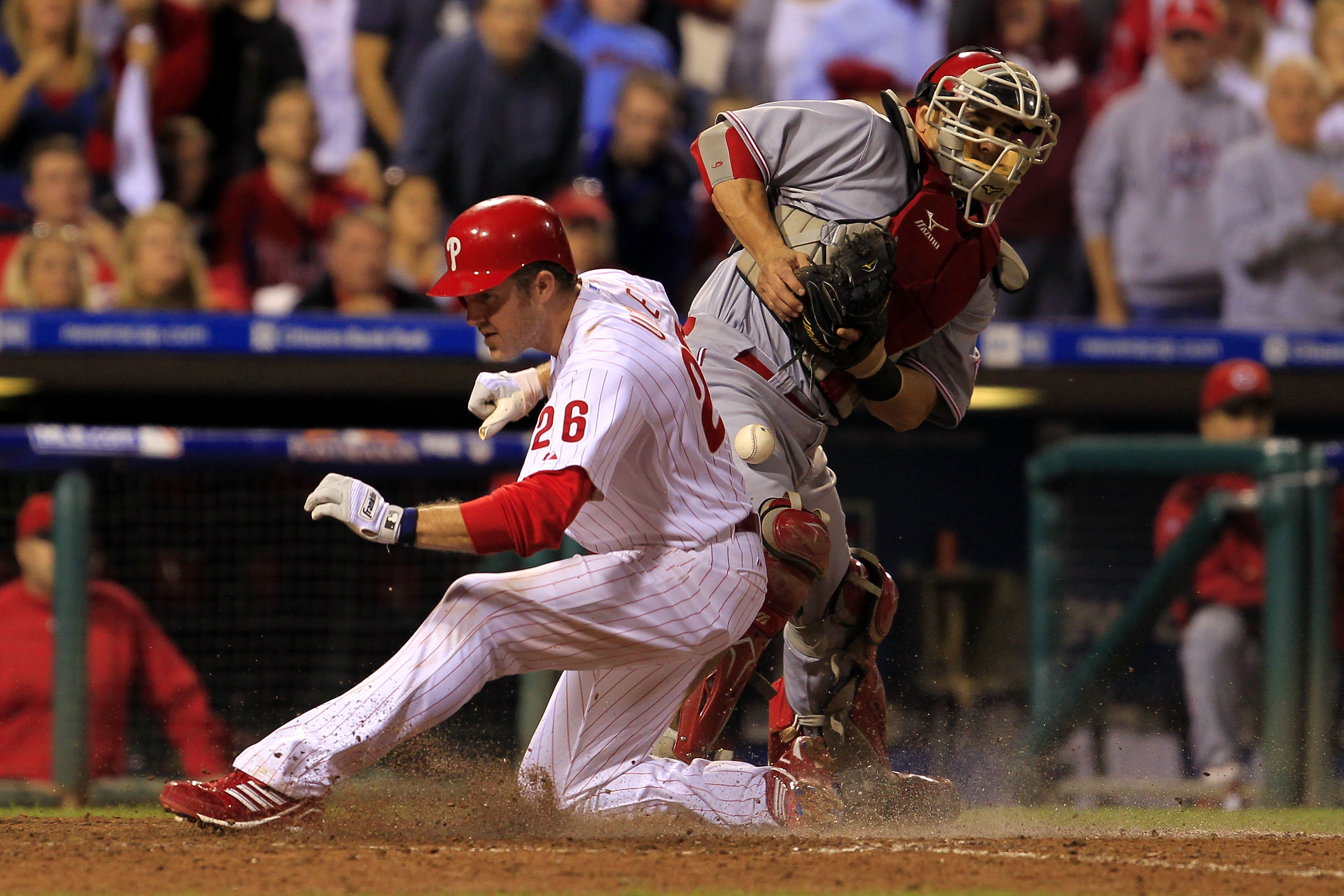 PHILADELPHIA - OCTOBER 08: Chase Utley #28 of the Philadelphia Phillies crosses the plate to score in front of Ryan Hanigan #29 of the Cincinnati Reds in game 2 of NLDS at Citizens Bank Park on October 8, 2010 in Philadelphia, Pennsylvania. The Phillies d
