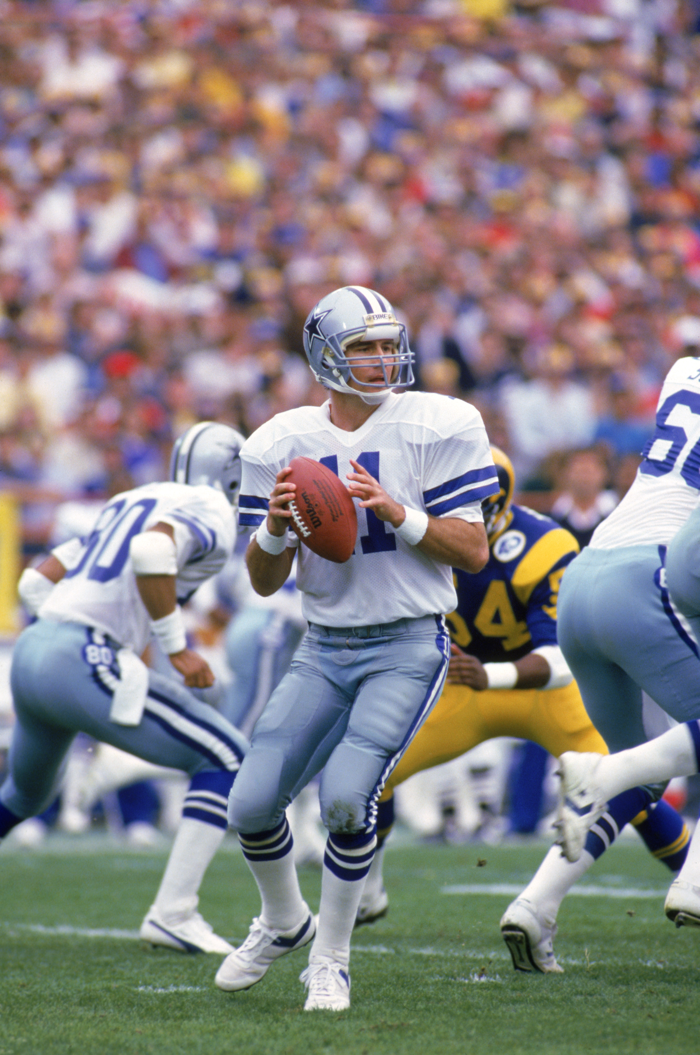 ANAHEIM, CA - JANUARY 4:  Quarterback Danny White #11 of the Dallas Cowboys looks to pass during a 1985 NFC Divisional Playoff game against the Los Angeles Rams at Anaheim Stadium on January 4, 1996 in Anaheim, California.  The Rams won 20-0.  (Photo by G