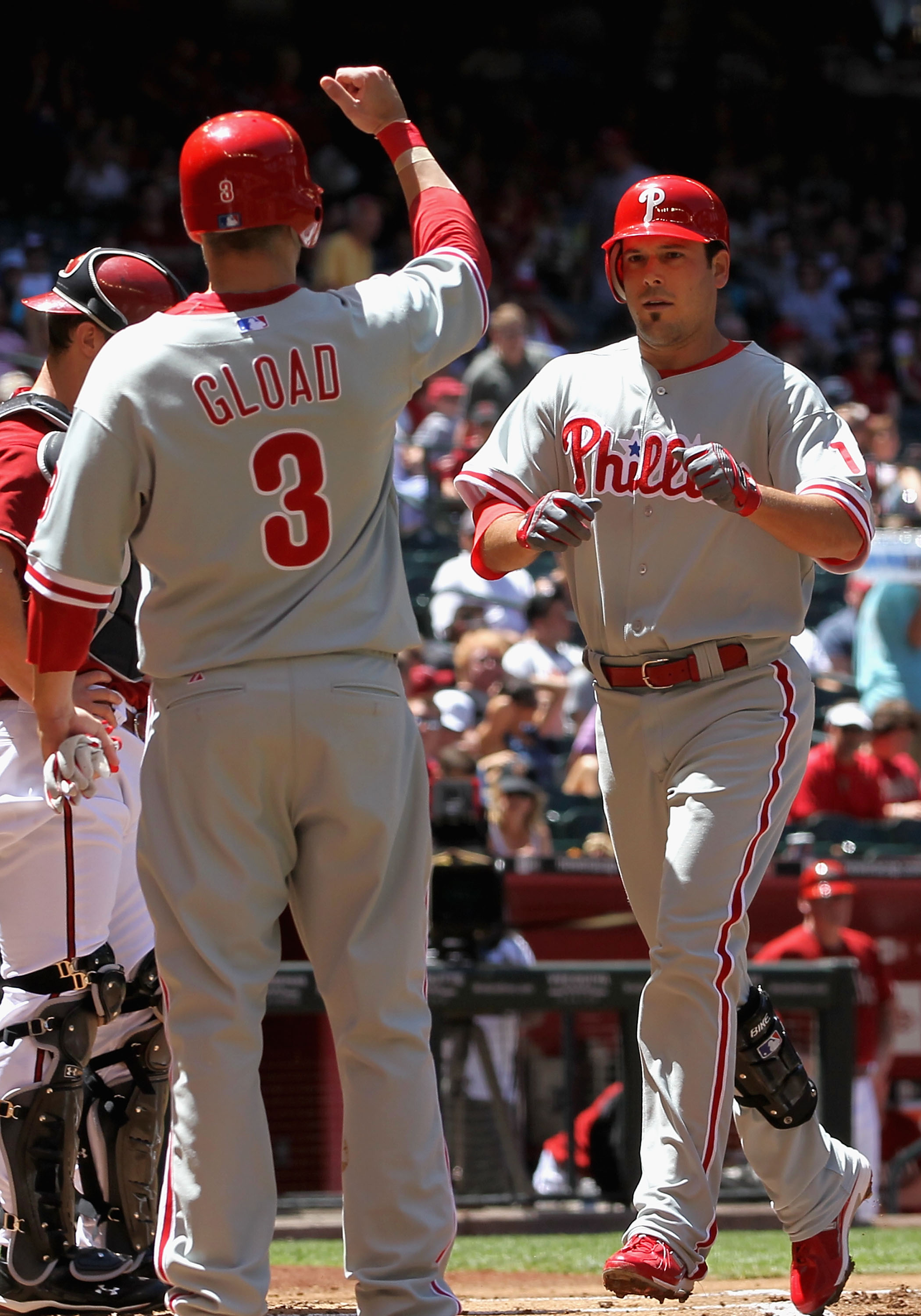 PHOENIX - APRIL 25:  Greg Dobbs #19 of the Philadelphia Phillies is congratulated by teammate Ross Gload #3 after Dobbs hit a 2 run home run against the Arizona Diamondbacks during the first inning of the Major League Baseball game at Chase Field on April