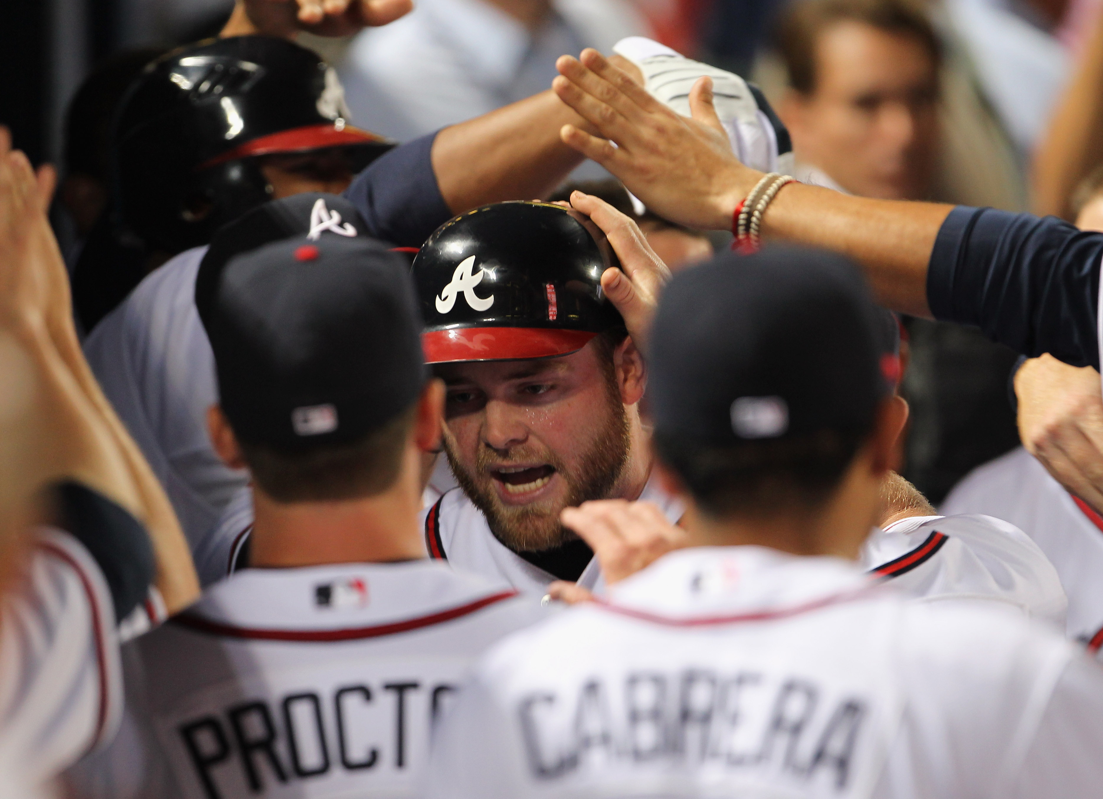 ATLANTA - OCTOBER 11:  Brian McCann #16 of the Atlanta Braves is congratulated by teammates after hitting a solo home run during the 6th inning of Game Four of the NLDS of the 2010 MLB Playoffs against the San Francisco Giants on October 11, 2010  at Turn