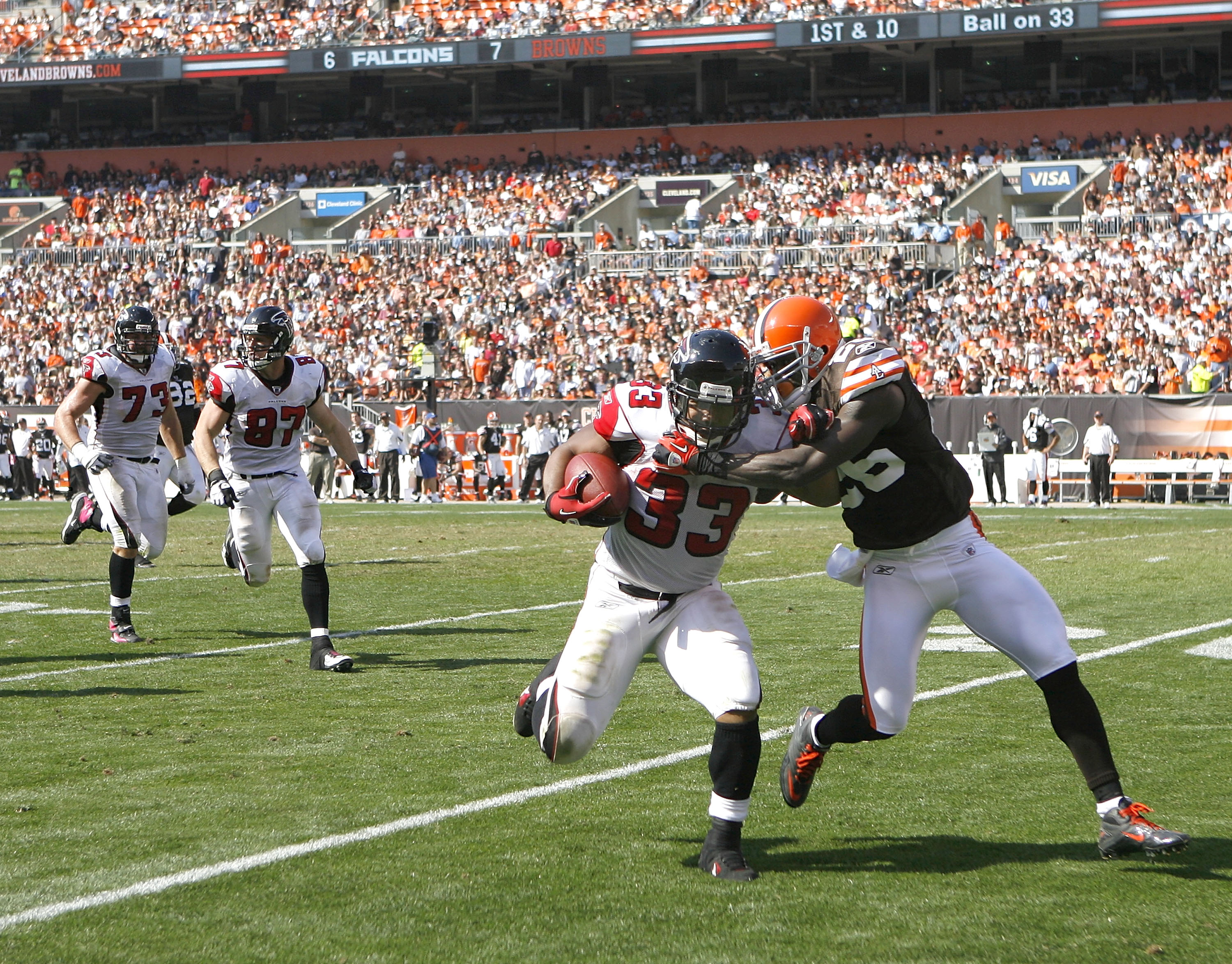 CLEVELAND - OCTOBER 10:  Running back Michael Turner #33 of the Atlanta Falcons runs the ball as he is hit by defensive back Abram Elam #26 of the Cleveland Browns at Cleveland Browns Stadium on October 10, 2010 in Cleveland, Ohio.  (Photo by Matt Sulliva