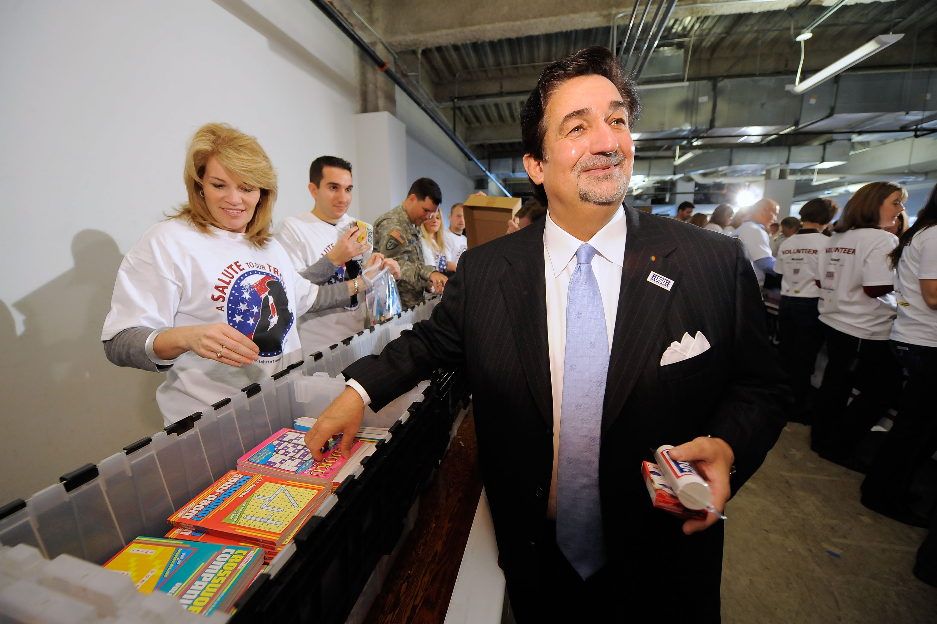 ARLINGTON, VA - NOVEMBER 09:  Teresa Carlson, Vice President US Federal Government Microsoft Corporation and Ted Leonsis, owner of the Washington Capitols joins volunteers in creating care packages for active duty US Military personal serving in Iraq and