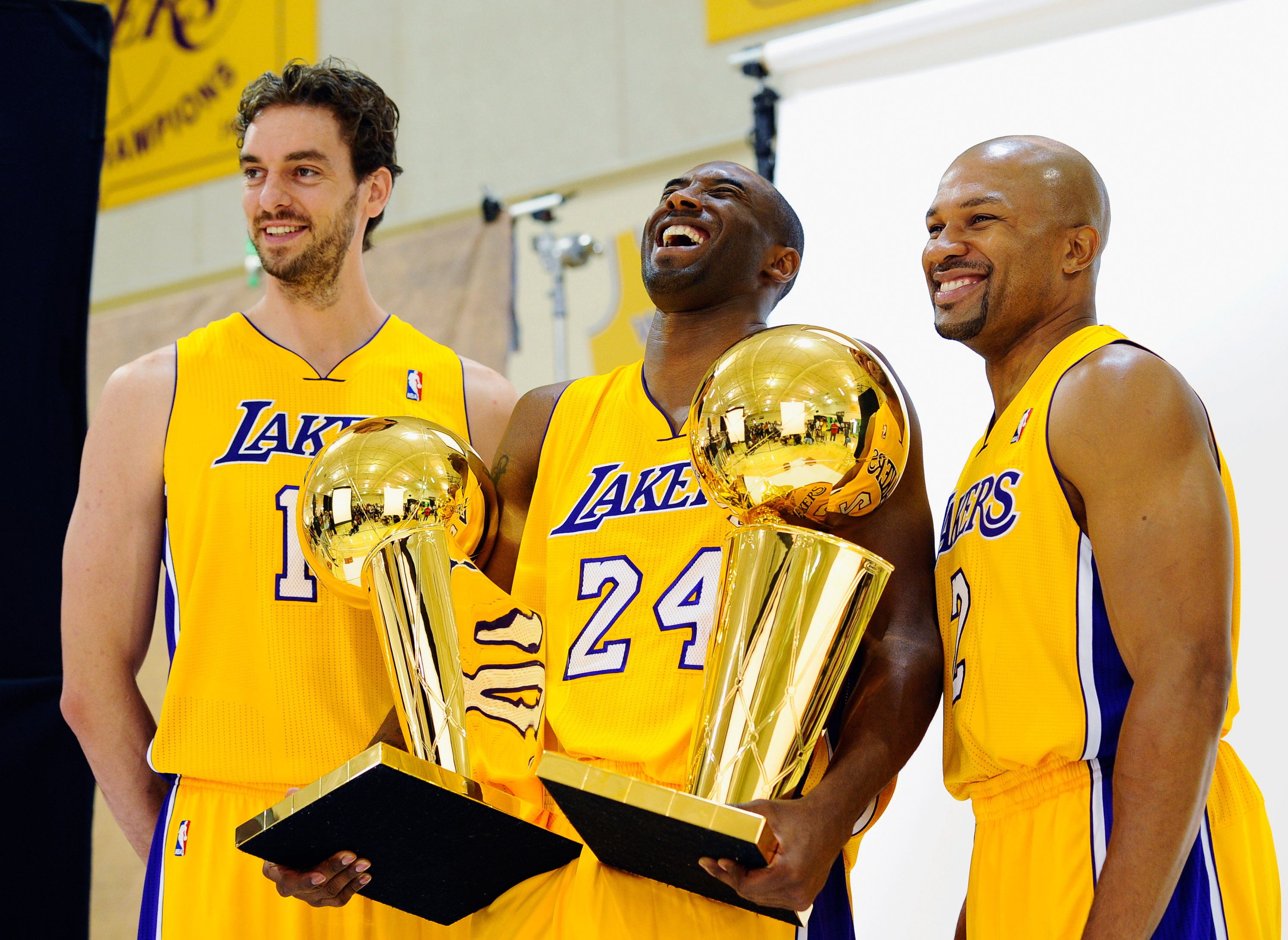 EL SEGUNDO, CA - SEPTEMBER 25:  Kobe Bryant #24  of the Los Angeles Lakers laughs as he holds two NBA Finals Larry O'Brien Championship Trophy's as he poses for a photograph with teammates Pau Gasol #16 and Derek Fisher #2 during Media Day at the Toyota C