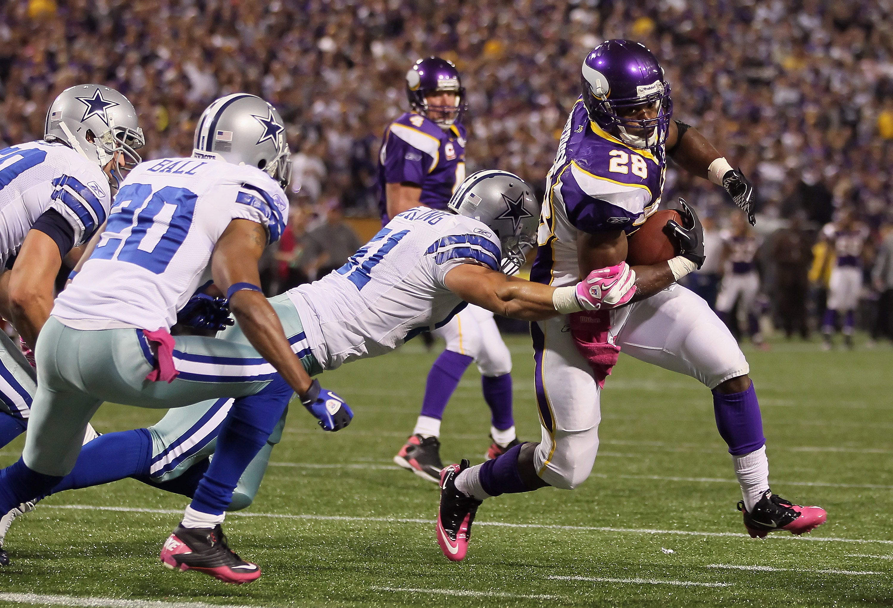 MINNEAPOLIS - OCTOBER 17:  Running back Adrian Peterson #29 of the Minnesota Vikings breaks a tackle from Keith Brooking #51 of the Dallas Cowboys for a touchdown during the third quarter at Mall of America Field on October 17, 2010 in Minneapolis, Minnes