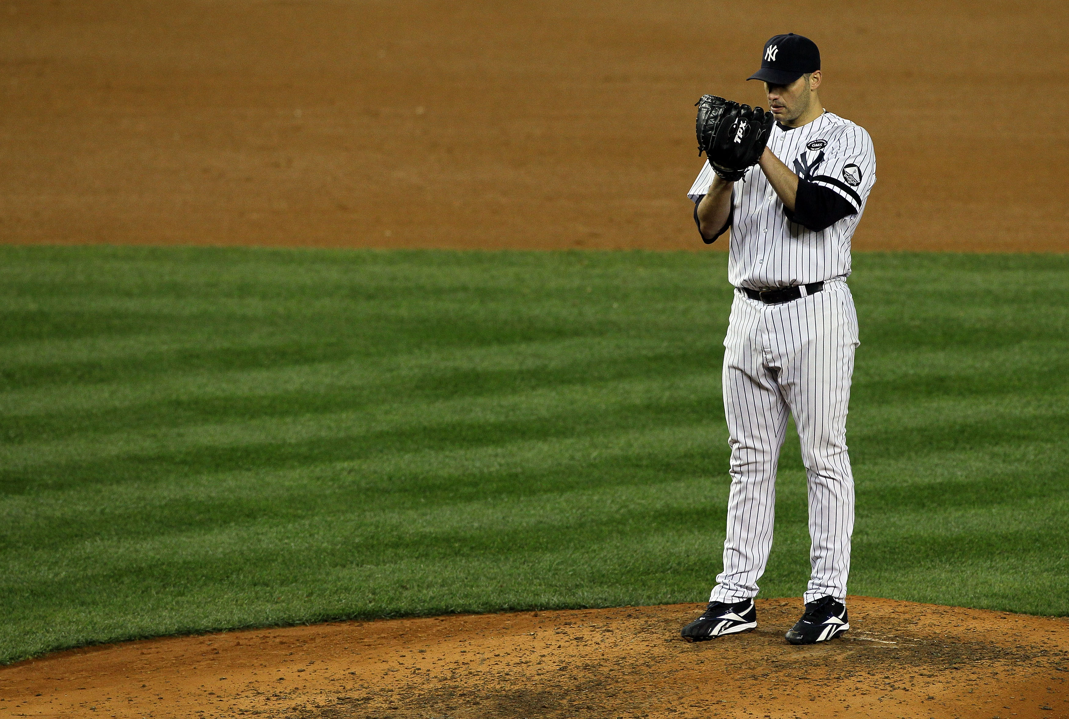 NEW YORK - OCTOBER 18:  Starting pitcher Andy Pettitte #46 of the New York Yankees gets set to throw a pitch against the Texas Rangers in Game Three of the ALCS during the 2010 MLB Playoffs at Yankee Stadium on October 18, 2010 in New York, New York.  (Ph