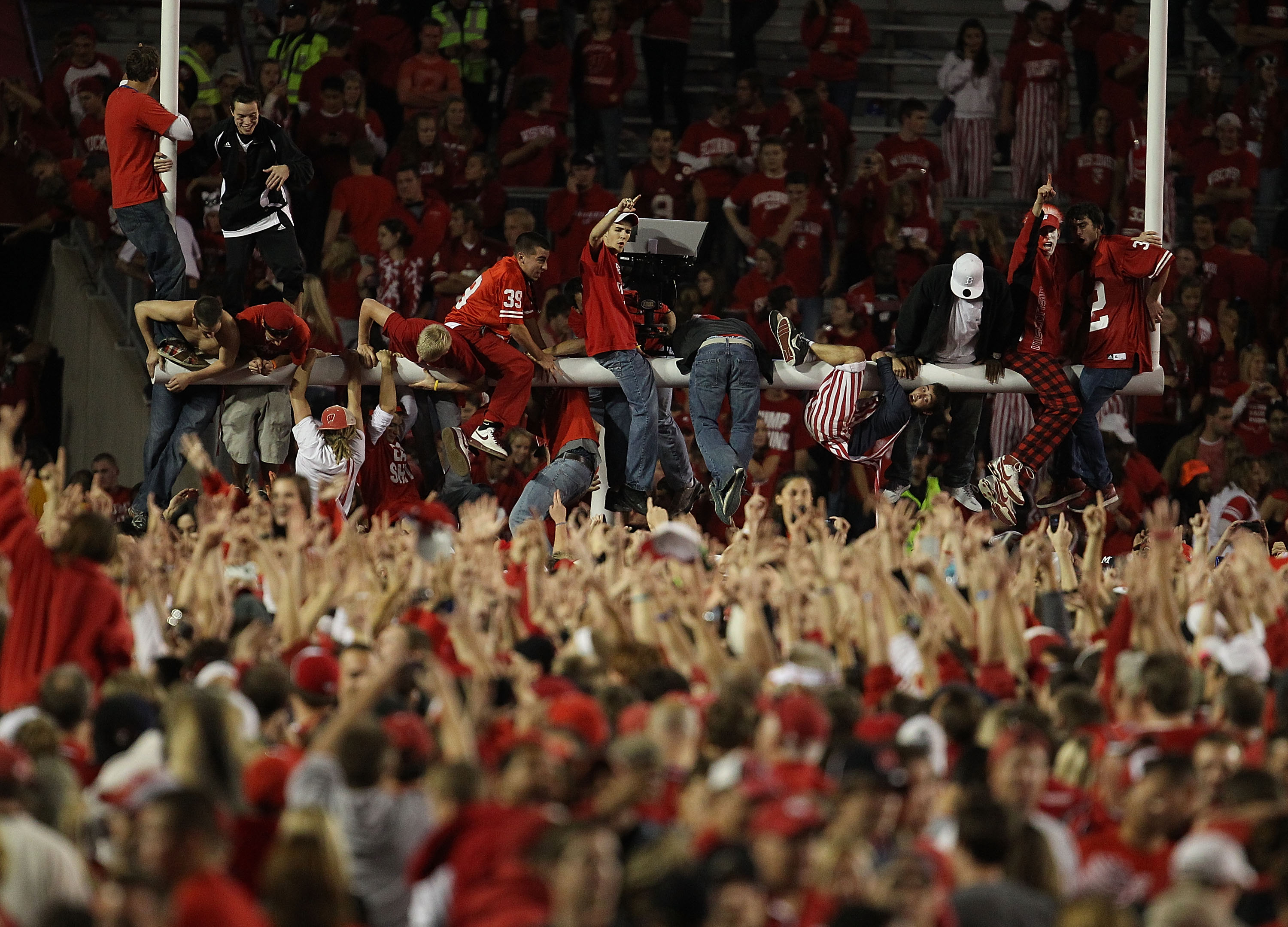 MADISON, WI - OCTOBER 16: Fans of the Wisconsin Badgers storm the field and climb the goal post after a win over the Ohio State Buckeyes at Camp Randall Stadium on October 16, 2010 in Madison, Wisconsin. Wisconsin defeated Ohio State 31-18. (Photo by Jona