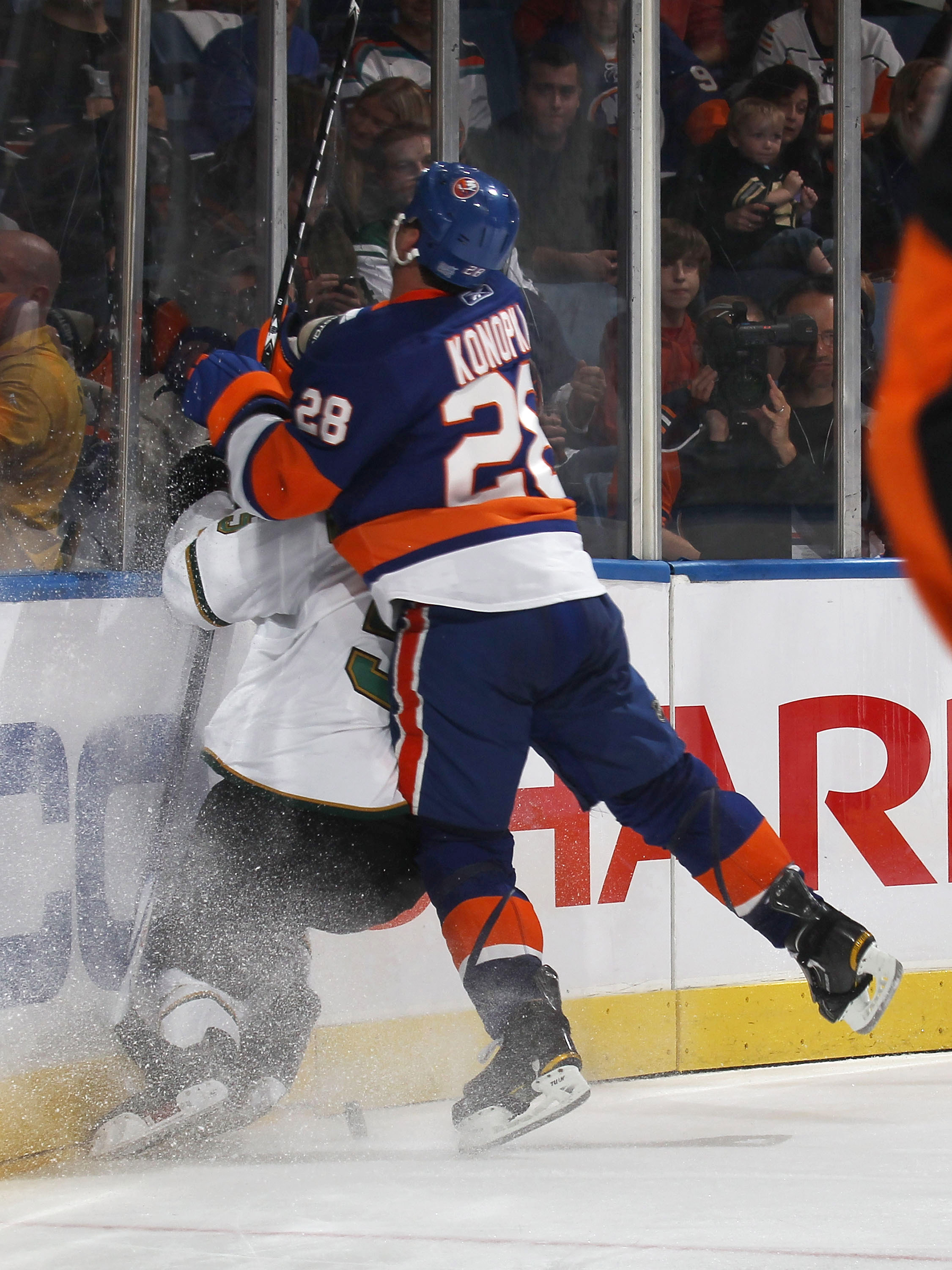 UNIONDALE, NY - OCTOBER 09:  Zenon Konopka #28 of the New York Islanders checks a Dallas Star in a game at the Nassau Coliseum on October 9, 2010 in Uniondale, New York.  (Photo by Bruce Bennett/Getty Images)