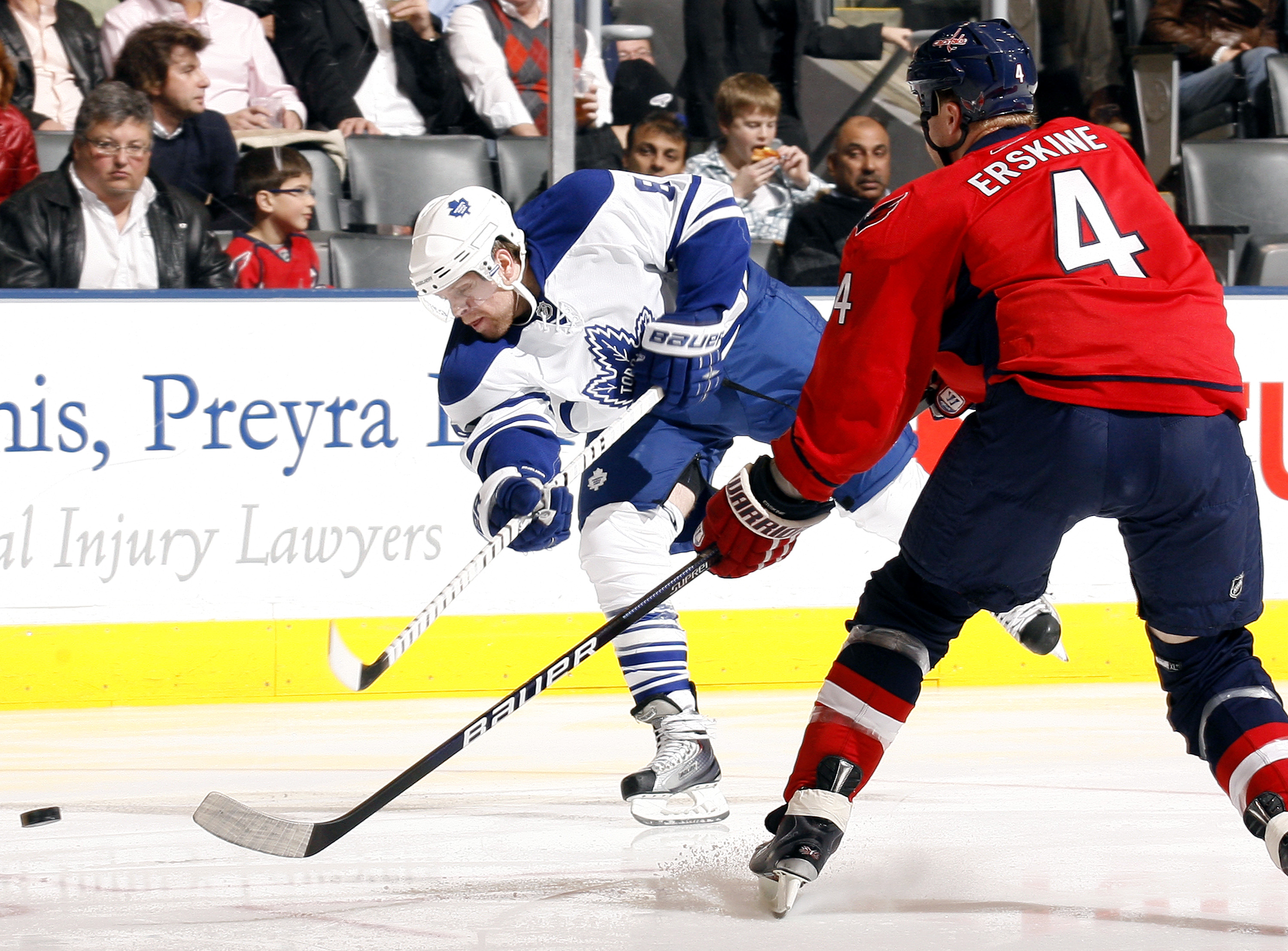 TORONTO - NOVEMBER 21:  Phil Kessel #81 of the Toronto Maple Leafs shoots past John Erskine #4 of the Washington Capitals during game action November 21, 2009 at the Air Canada Centre in Toronto, Ontario, Canada. (Photo by Abelimages/Getty Images)