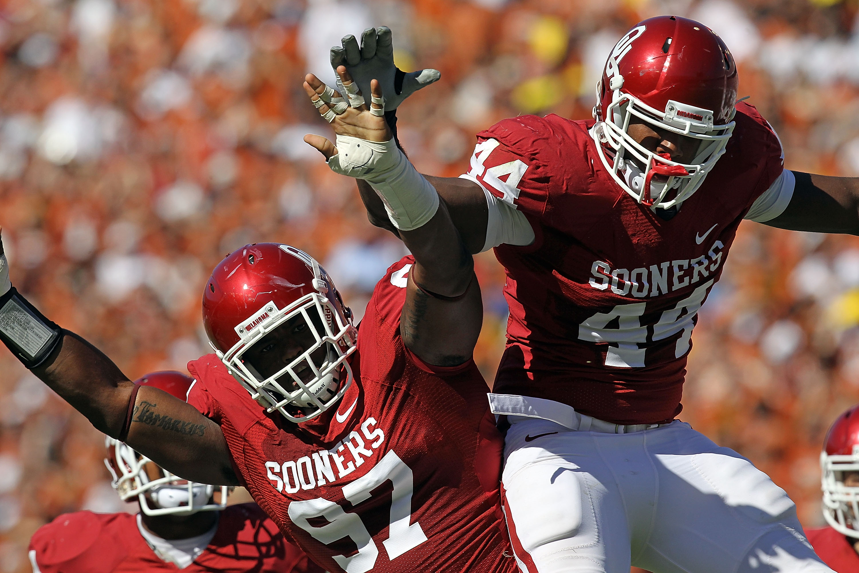DALLAS - OCTOBER 02:  Jeremy Beal #44 and Jamarkus McFarland #97 of the Oklahoma Sooners celebrate a quarterback sack against the Texas Longhorns in the first quarter at the Cotton Bowl on October 2, 2010 in Dallas, Texas.  (Photo by Ronald Martinez/Getty