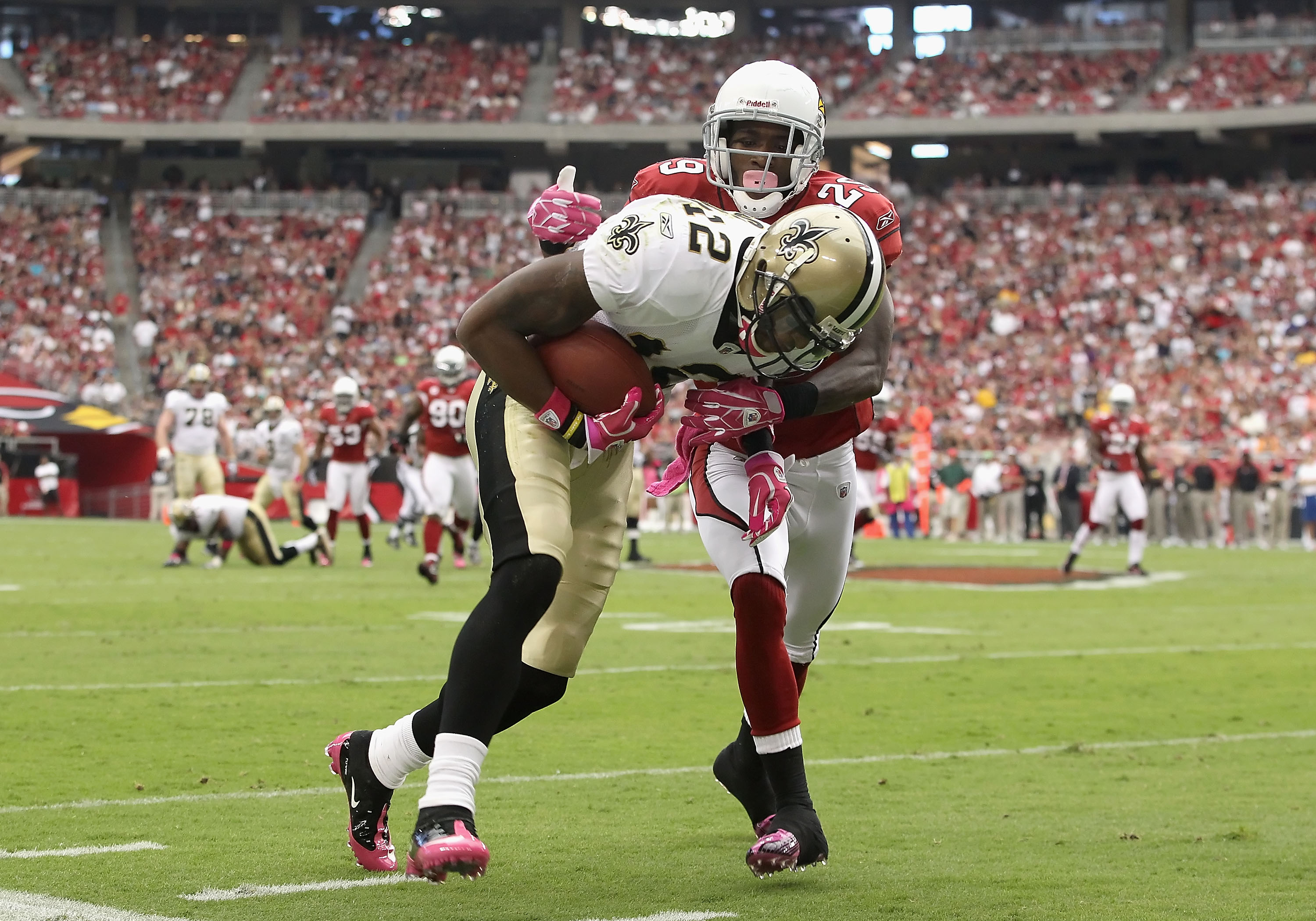 GLENDALE, AZ - OCTOBER 10:  Wide receiver Marques Colston #12 of the New Orleans Saints is tackled by Dominique Rodgers-Cromartie #29 of the Arizona Cardinals after a reception during the first quarter of the NFL game at the University of Phoenix Stadium