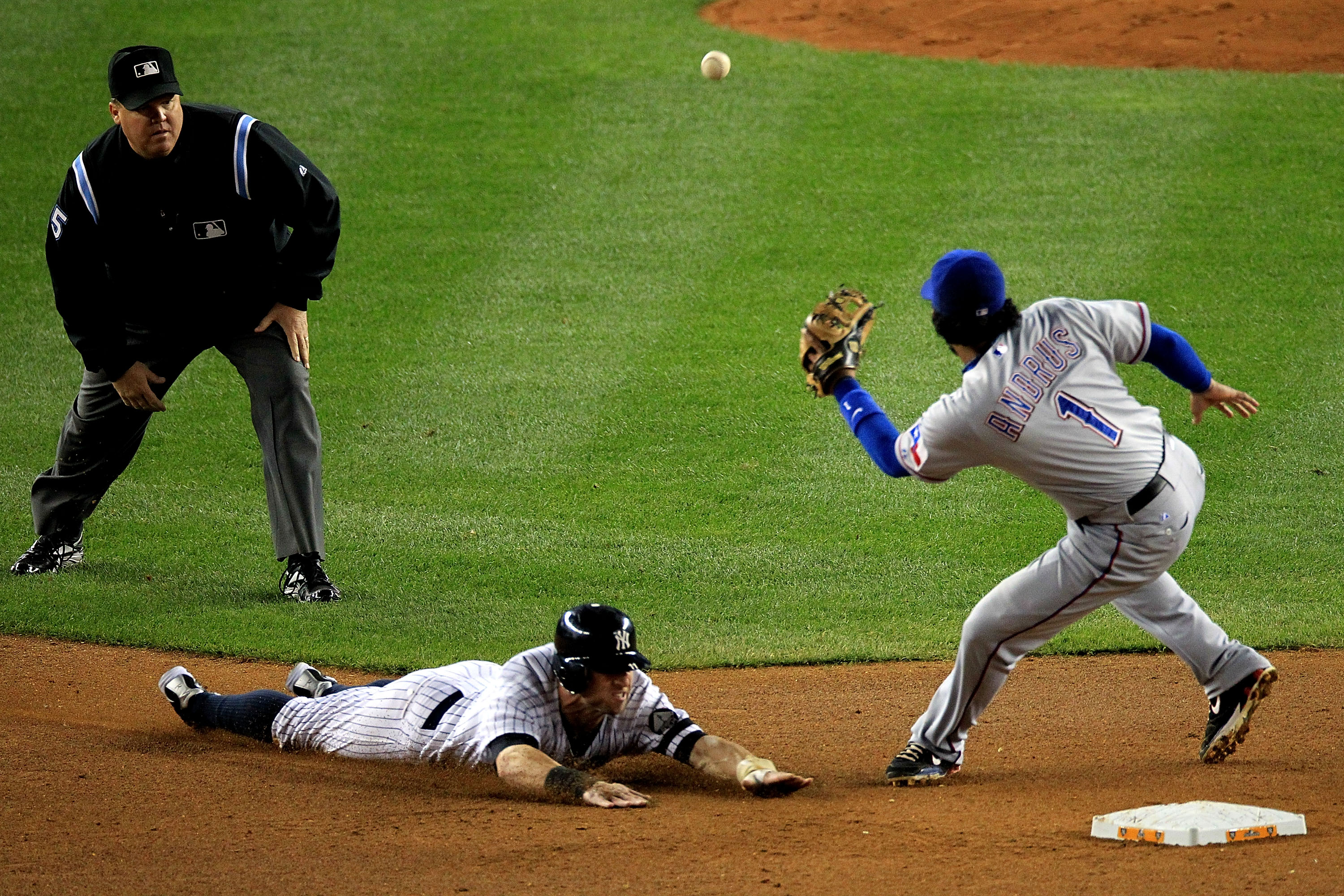 NEW YORK - OCTOBER 18:  Brett Gardner #11 of the New York Yankees steals second base as Elvis Andrus #1 of the Texas Rangers fails to field throw during Game Three of the ALCS during the 2010 MLB Playoffs at Yankee Stadium on October 18, 2010 in New York,