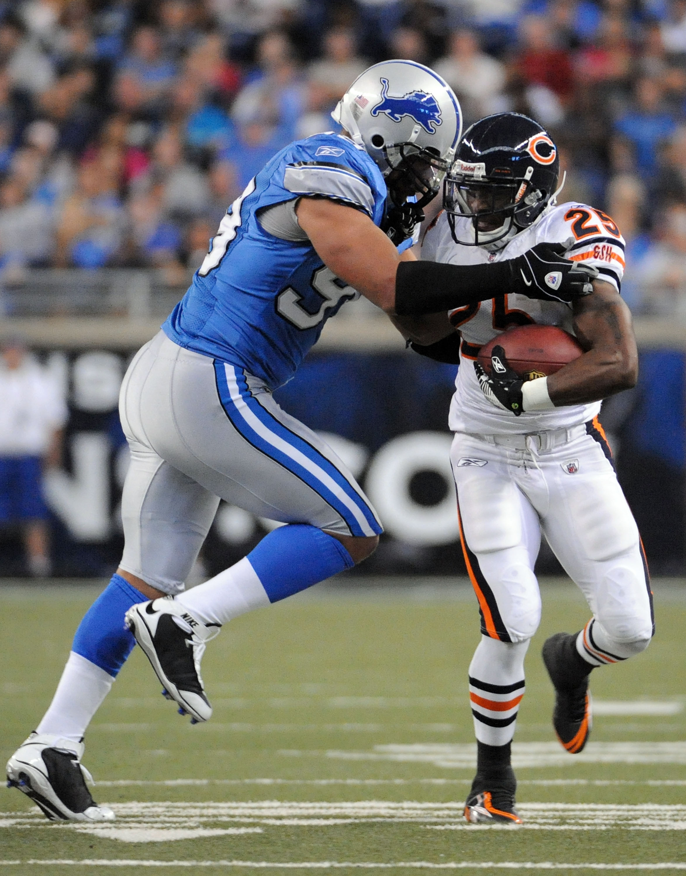 DETROIT - OCTOBER 05:  Garrett Wolfe #25 of the Chicago Bears is tackled by Dewayne White #99 of the Detroit Lions during the first quarter at Ford Field on October 5, 2008 in Detroit, Michigan.  The Bears won 34-7.  (Photo by Harry How/Getty Images)