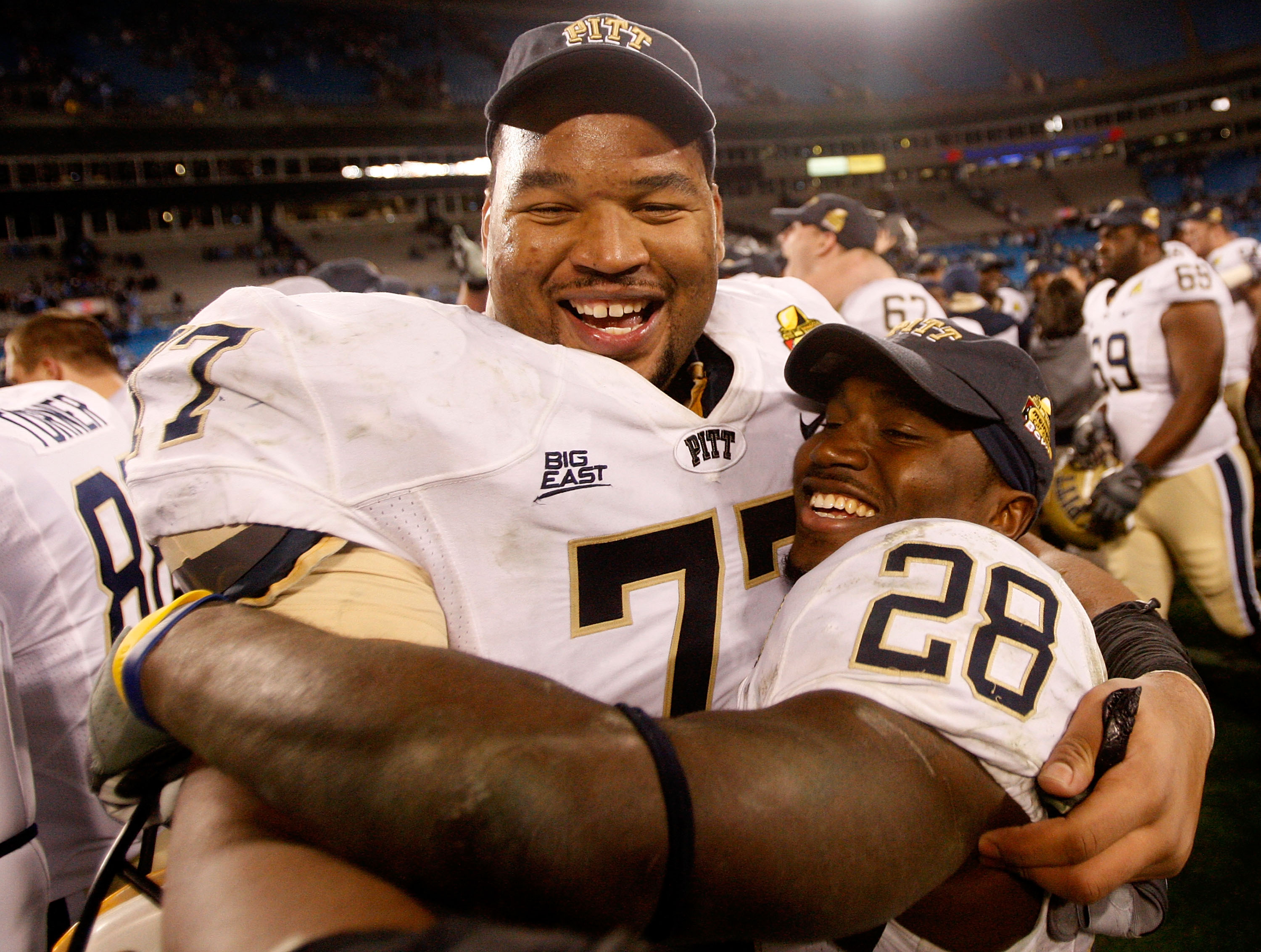 CHARLOTTE, NC - DECEMBER 26:  Teammates Jason Pinkston #77 and Dion Lewis #28 of the Pittsburgh Panthers celebrates after a 19-17 victory over the North Carolina Tar Heels on December 26, 2009 in Charlotte, North Carolina.  (Photo by Streeter Lecka/Getty