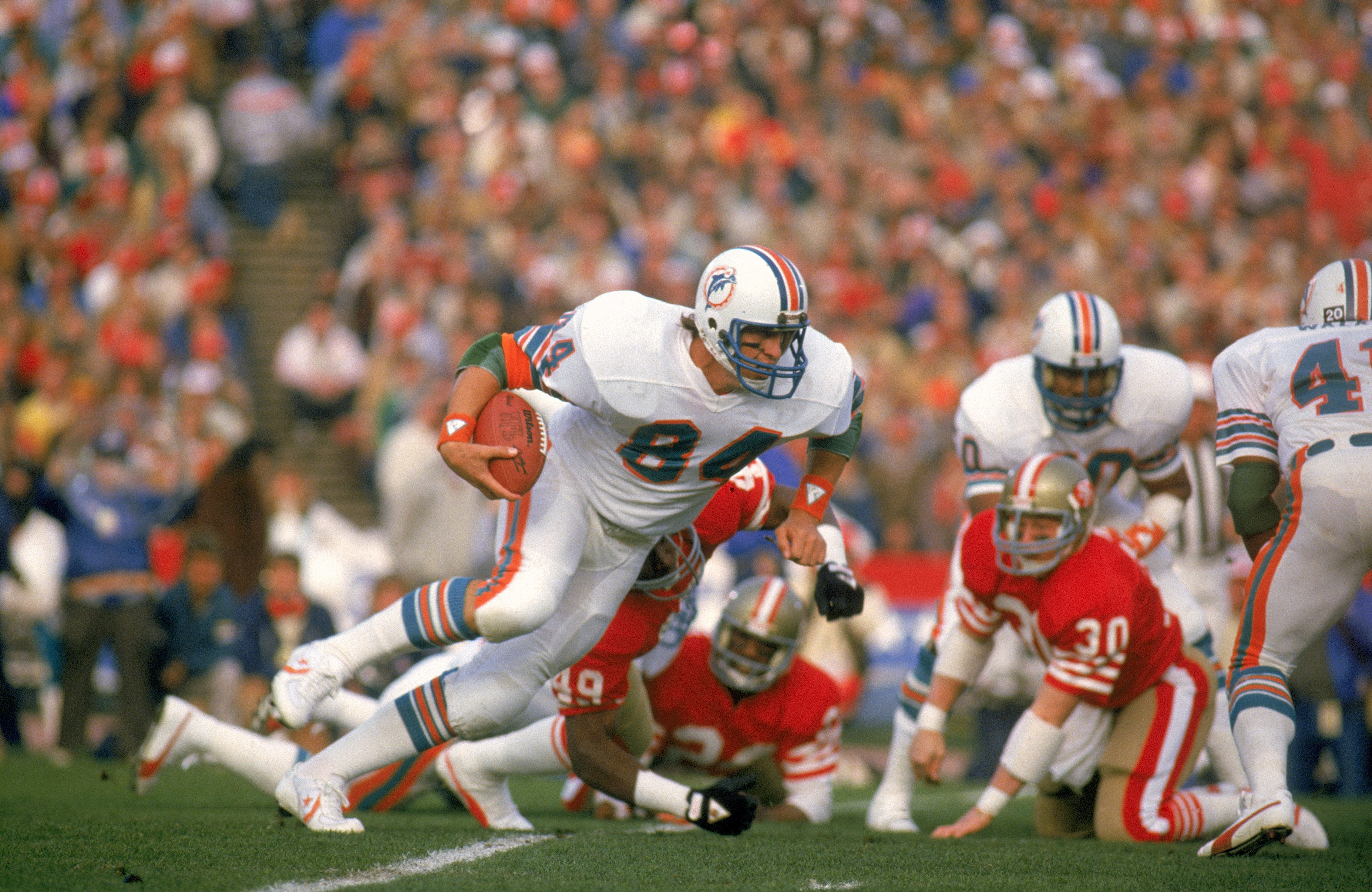 STANFORD, CA - JANUARY 20:  Bruce Hardy #84 of the Miami Dolphins runs with the ball during Super Bowl XIX against the San Francisco 49ers at Stanford Stadium on January 20, 1985 in Stanford, California.  The 49ers defeated the Dolphins 38-16.  (Photo by