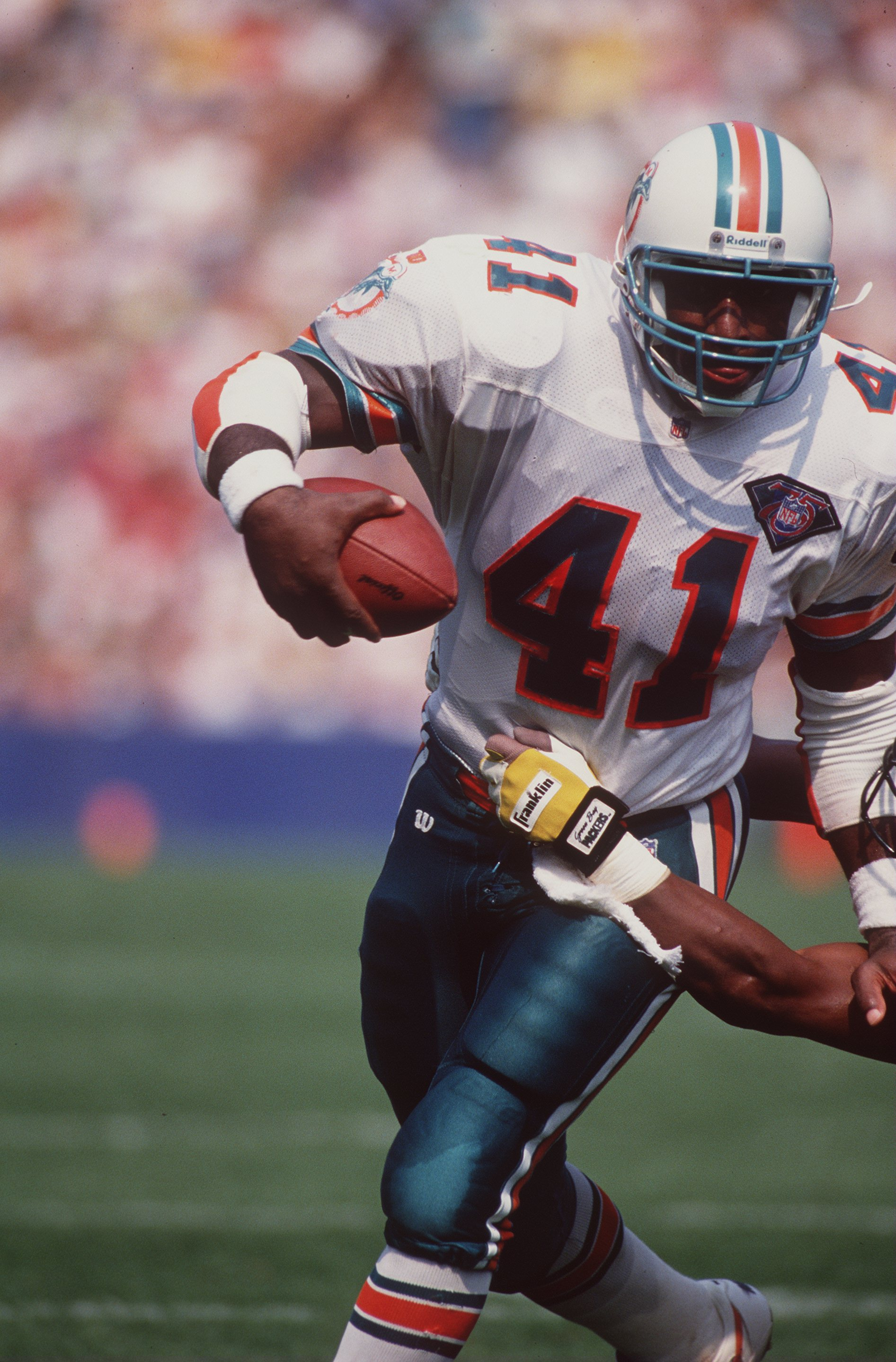 11 Sep 1994:  Running back Keith Byars of the Miami Dolphins looks up field as he uses his left arm to fend off an attempted tackle by a defensive player from the Green Bay Packers while running with the football during a carry in the Dolphins 24-14 victo