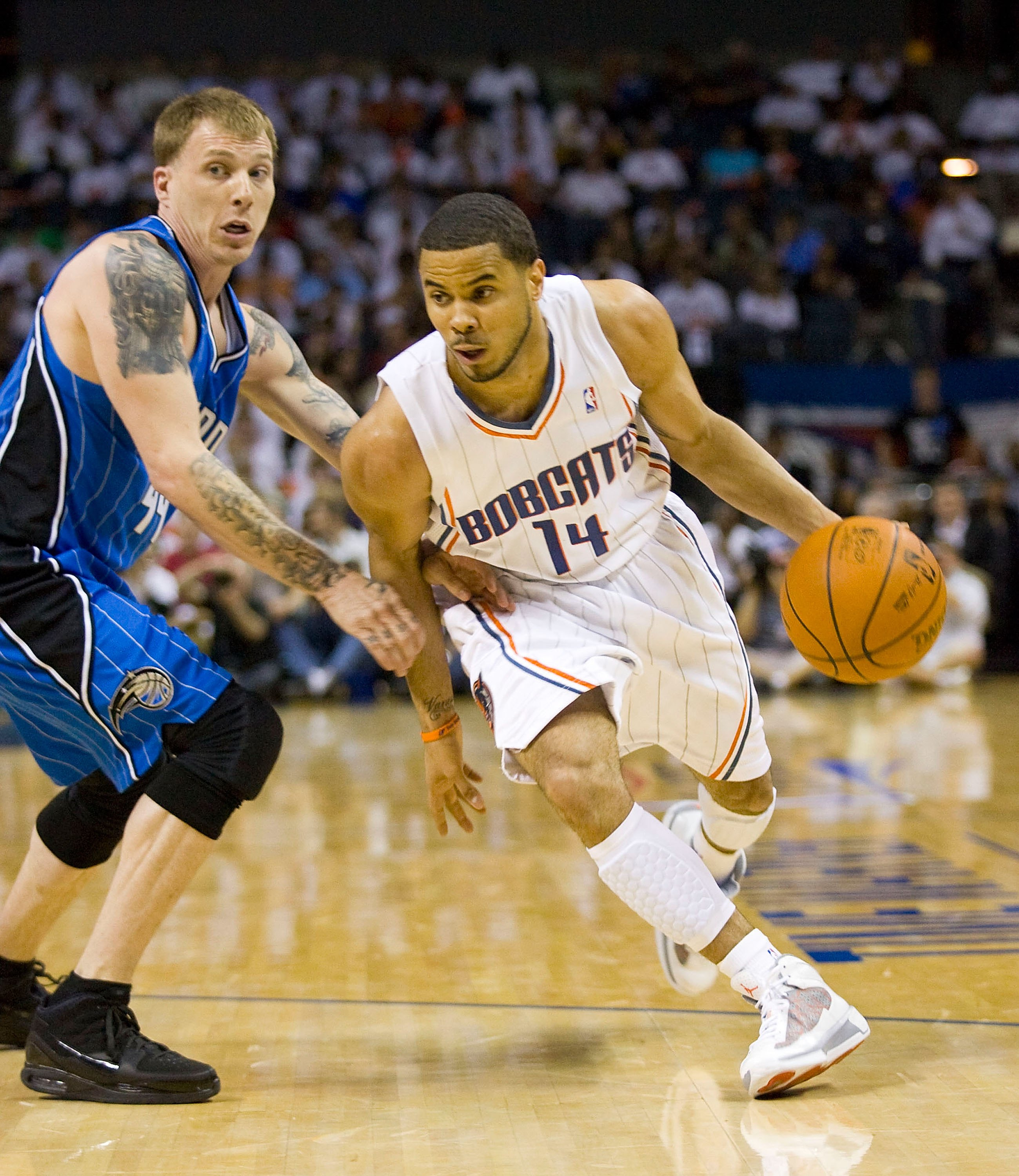 CHARLOTTE, NC - APRIL 26: D.J. Augustin #14 of the Charlotte Bobcats dribbles past Jason Williams #44 of the Orlando Magic at Time Warner Cable Arena on April 26, 2010 in Charlotte, North Carolina.  The Magic defeated the Bobcats 99-90 to complete the fou
