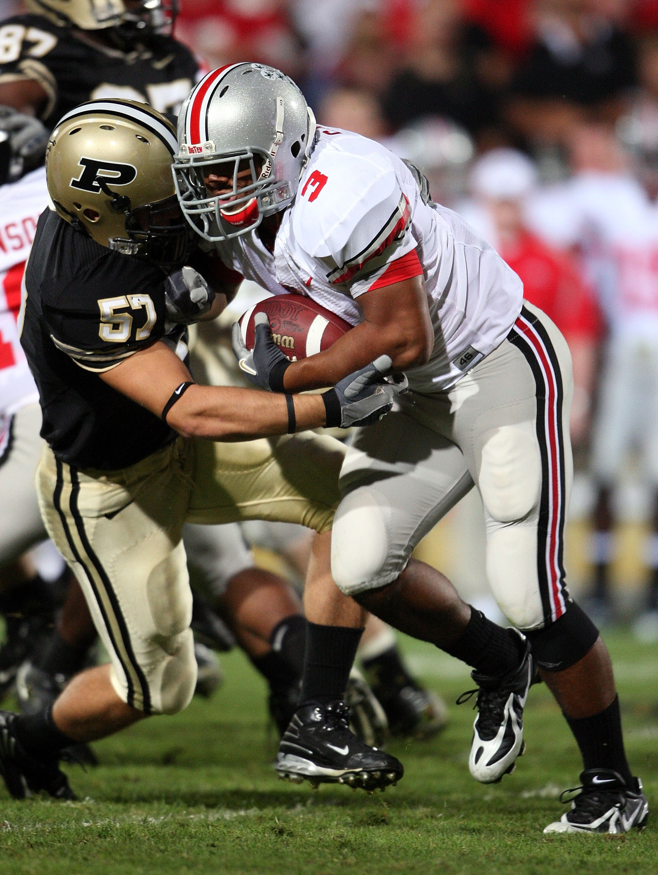 WEST LAFAYETTE, IN - OCTOBER 06:  Brandon Saine #3 of the Ohio State Buckeyes runs with the ball while defended by Tyler Haston #57 the Purdue Boilermakers during the game on October 6, 2007 at Ross-Ade Stadium in West Lafayette, Indiana.  (Photo by Andy