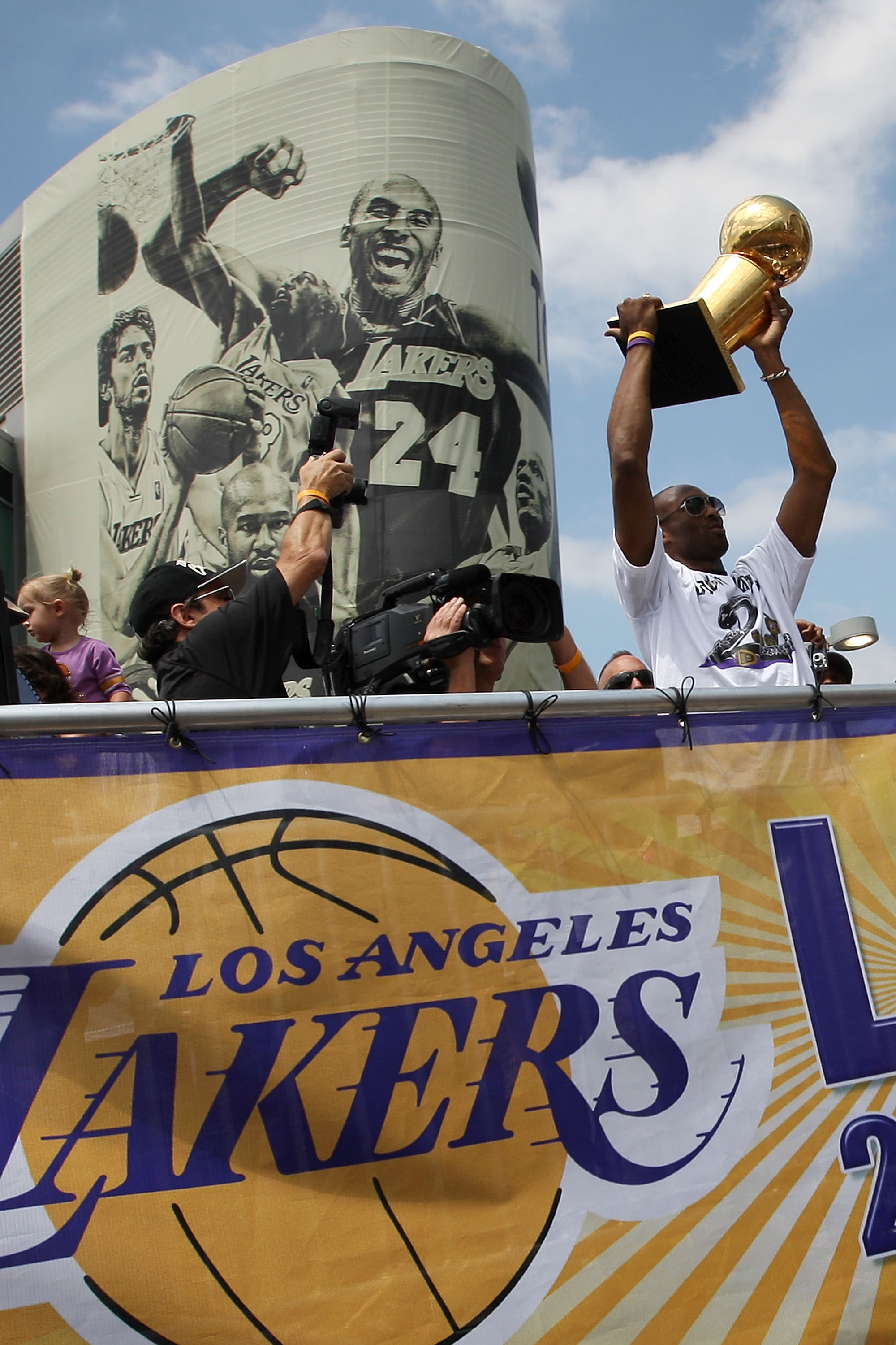LOS ANGELES, CA - JUNE 21:  Los Angeles Lakers guard Kobe Bryant hoists the championship trophy as he rides past a mural featuring himself during the victory parade for the the NBA basketball champion team on June 21, 2010 in Los Angeles, California. The