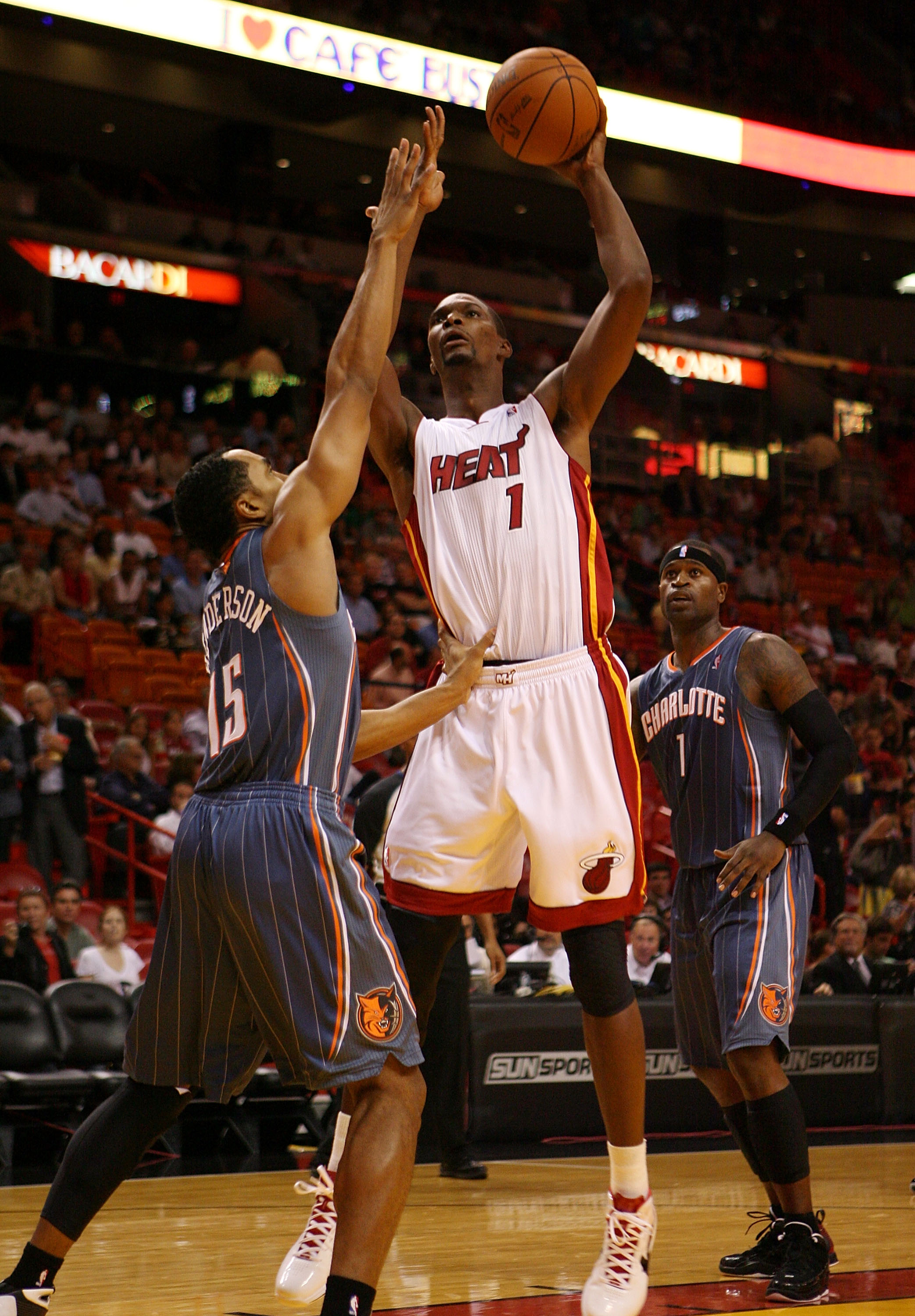 MIAMI - OCTOBER 18:  Center Chris Bosh #1 of the Miami Heat shoots over Guard Gerald Henderson #15  of the Charlotte Bobcats on October 18, 2010 at the American Airlines arena in Miami, Florida.  NOTE TO USER: User expressly acknowledges and agrees that,