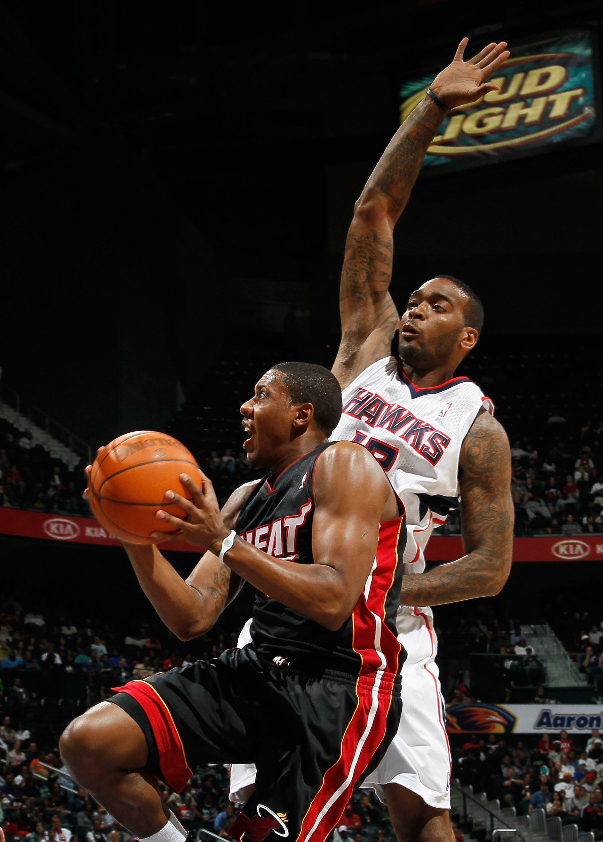 ATLANTA - OCTOBER 21:  Mario Chalmers #15 of the Miami Heat drives the basket against Josh Powell #12 of the Atlanta Hawks at Philips Arena on October 21, 2010 in Atlanta, Georgia.  (Photo by Kevin C. Cox/Getty Images)
