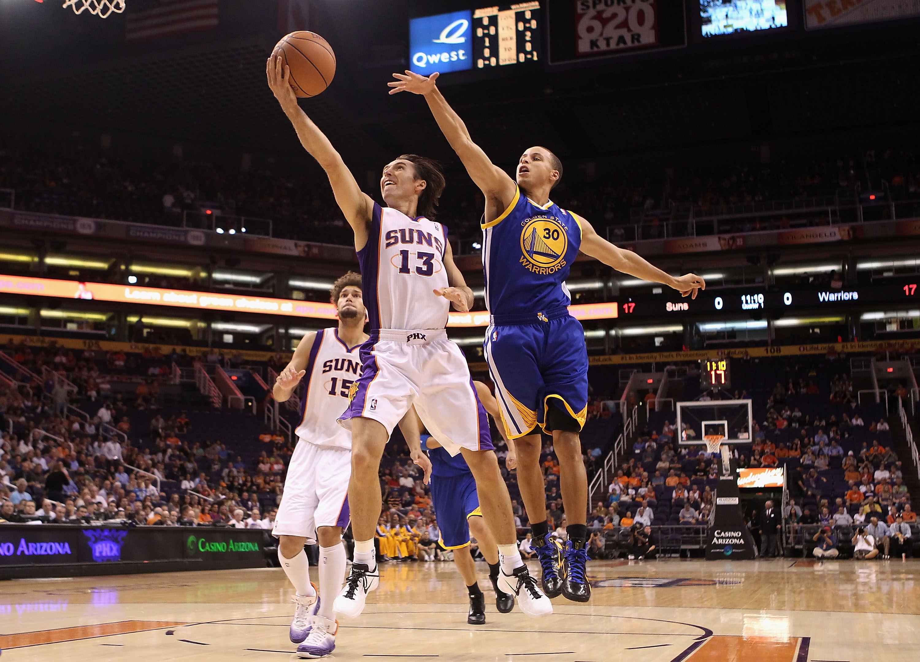 PHOENIX - OCTOBER 19:  Steve Nash #13 of the Phoenix Suns lays up a shot past Stephen Curry #30 of the Golden State Warriors during the preseason NBA game at US Airways Center on October 19, 2010 in Phoenix, Arizona. NOTE TO USER: User expressly acknowled