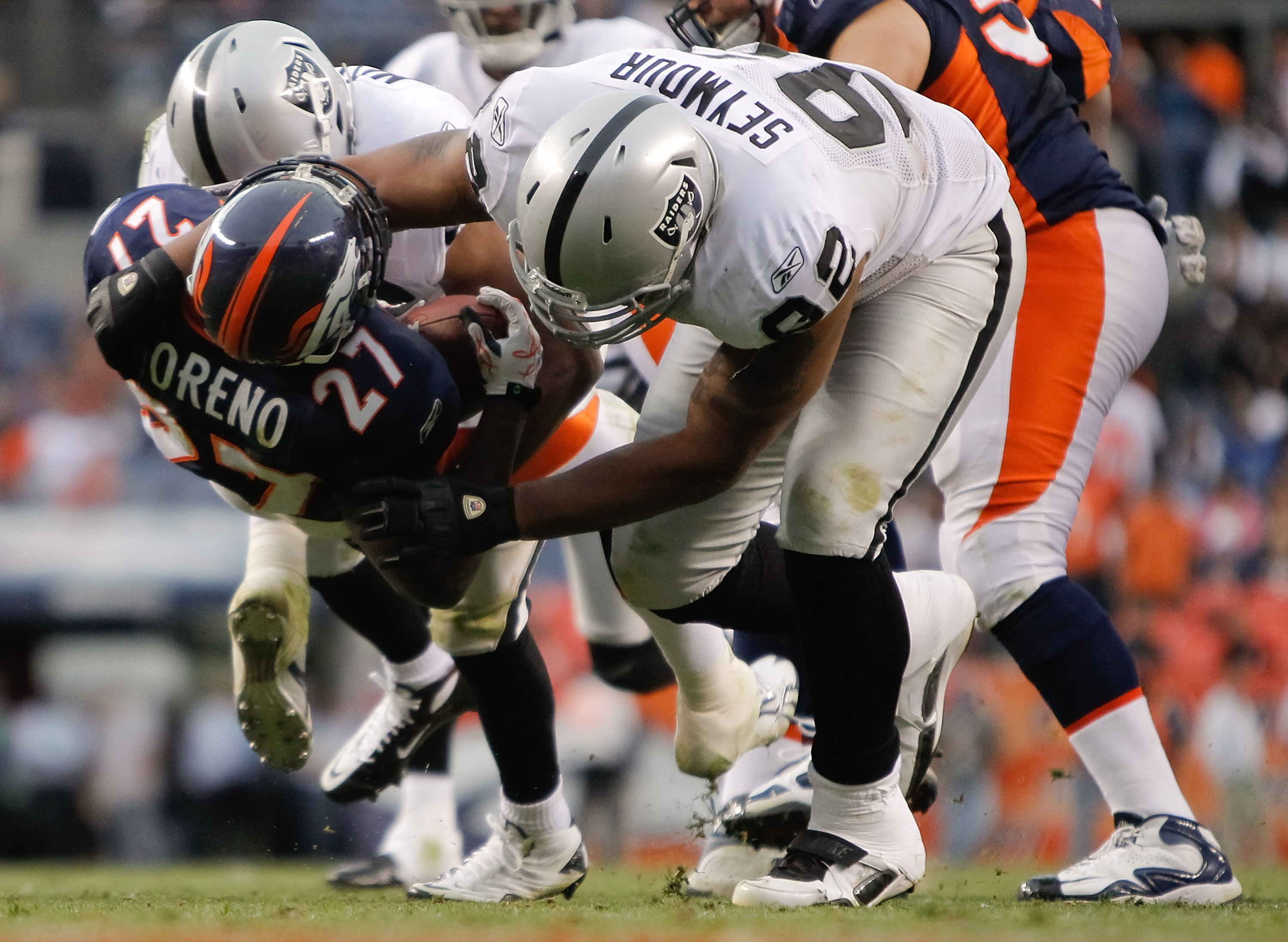 DENVER - OCTOBER 24:  Defensive end Richard Seymour #92 of the Oakland Raiders throws running back Knowshon Moreno #27 of the Denver Broncos to the ground in the fourth quarter at INVESCO Field at Mile High on October 24, 2010 in Denver, Colorado. The Rai
