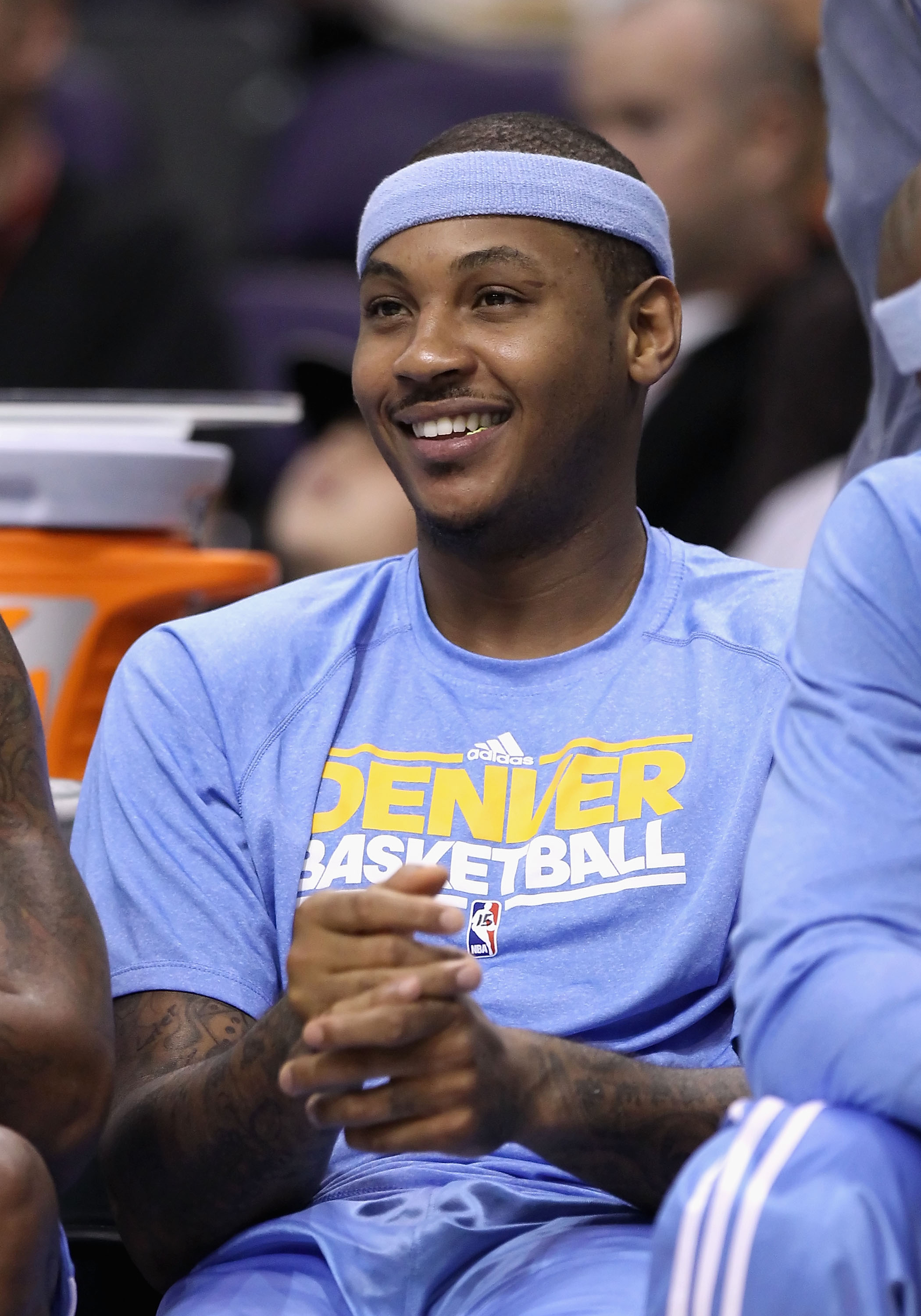 PHOENIX - OCTOBER 22:  Carmelo Anthony #15 of the Denver Nuggets smiles on the bench during the preseason NBA game against the Phoenix Suns at US Airways Center on October 22, 2010 in Phoenix, Arizona. NOTE TO USER: User expressly acknowledges and agrees