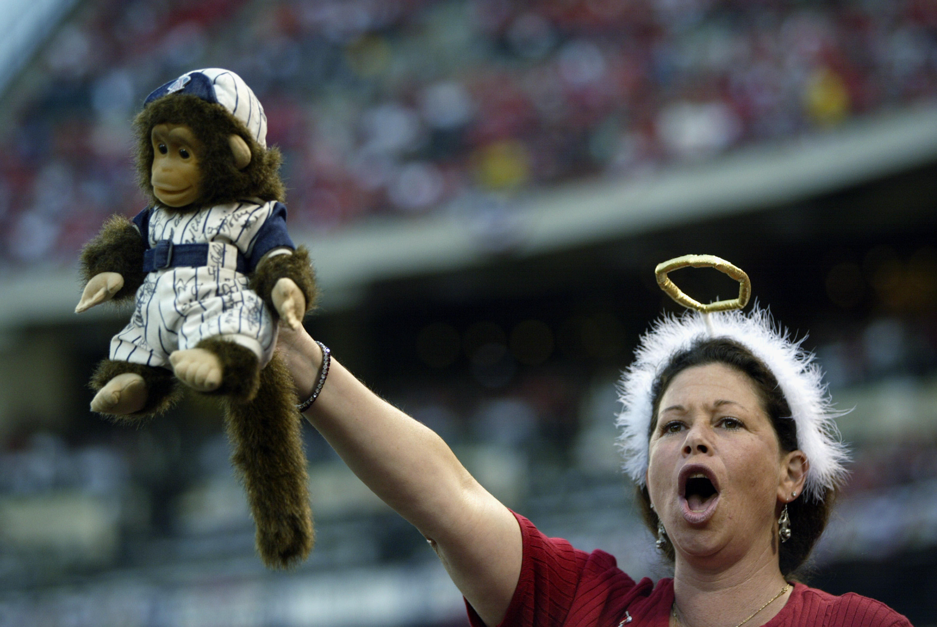 ANAHEIM, CA - OCTOBER 11:  A fan of the Anaheim Angels holds up a autographed 'rally monkey' stuffed animal during Game three of the American League Championship Series against the Minnesota Twins at Edison International Field on October 11, 2002 in Anahe