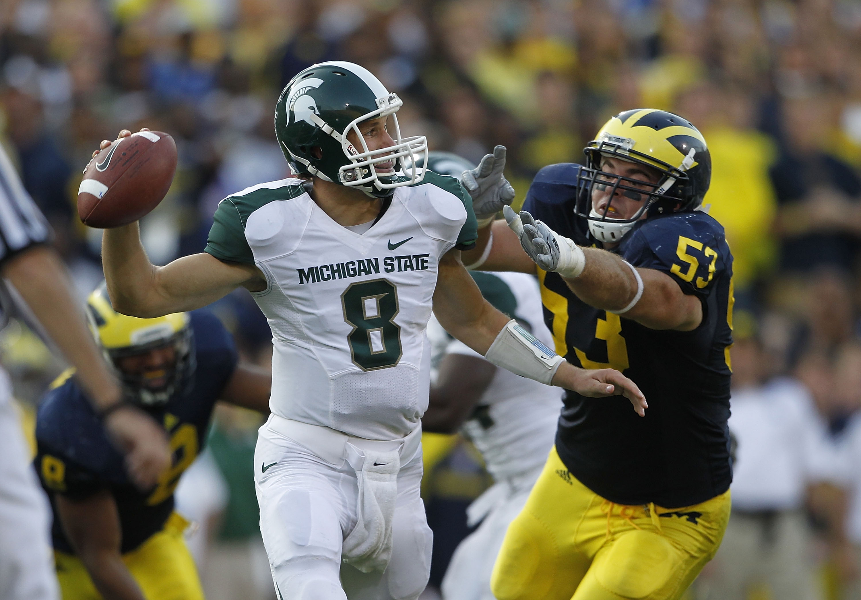 ANN ARBOR, MI - OCTOBER 09:  Kirk Cousins #8 of the Michigan State Spartans rolls out to pass as Ryan Van Bergen #53 of the Michigan Wolverines attempts to make the sack during the game on October 9, 2010 at Michigan Stadium in Ann Arbor, Michigan. The Mi