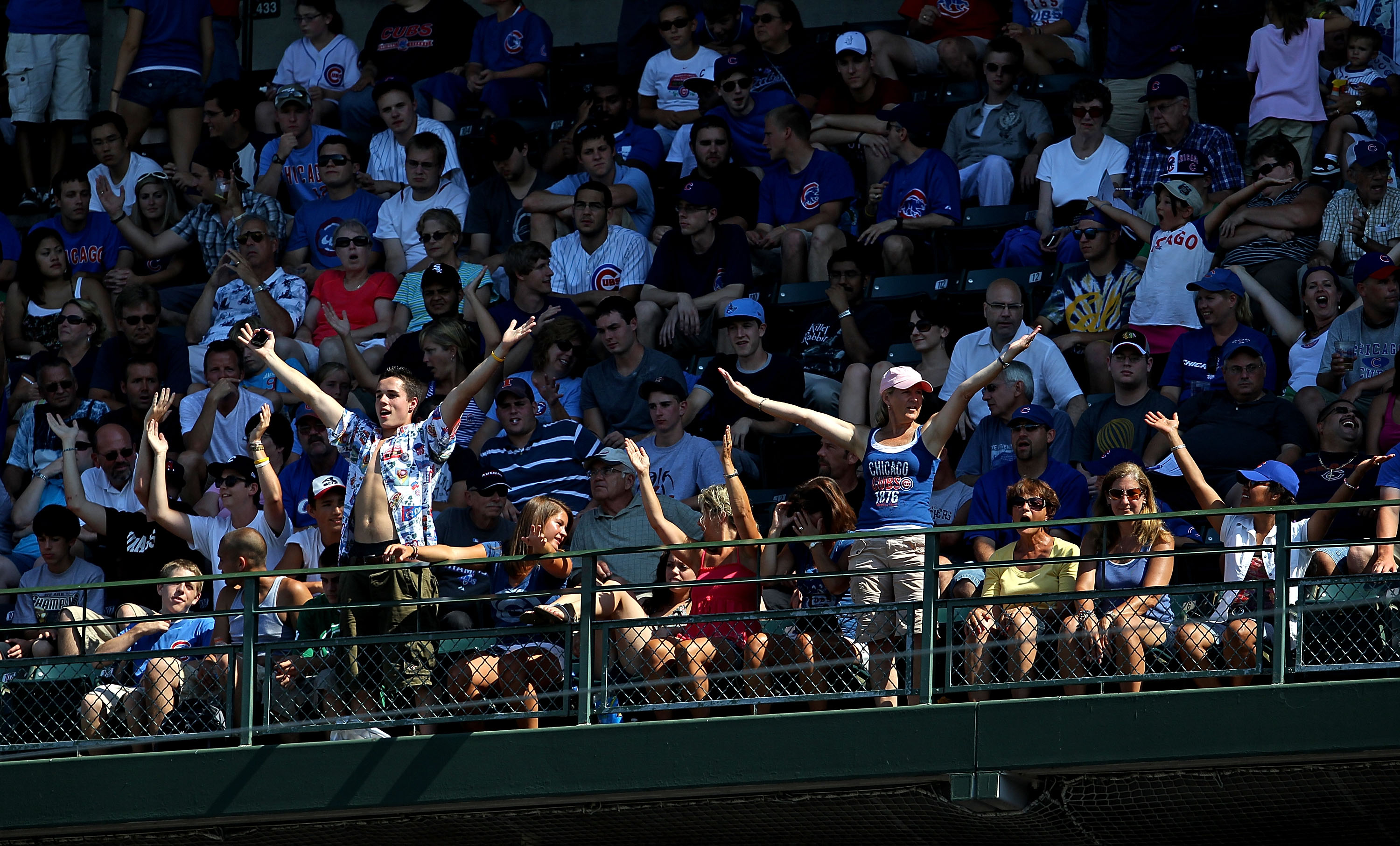 CHICAGO - JULY 21: Fans in the upper deck do a dance to the song 'YMCA' during a pitching change as the Chicago Cubs take on the Houston Astros at Wrigley Field on July 21, 2010 in Chicago, Illinois. The Astros defeated the Cubs 4-3 in 12 innings. (Photo