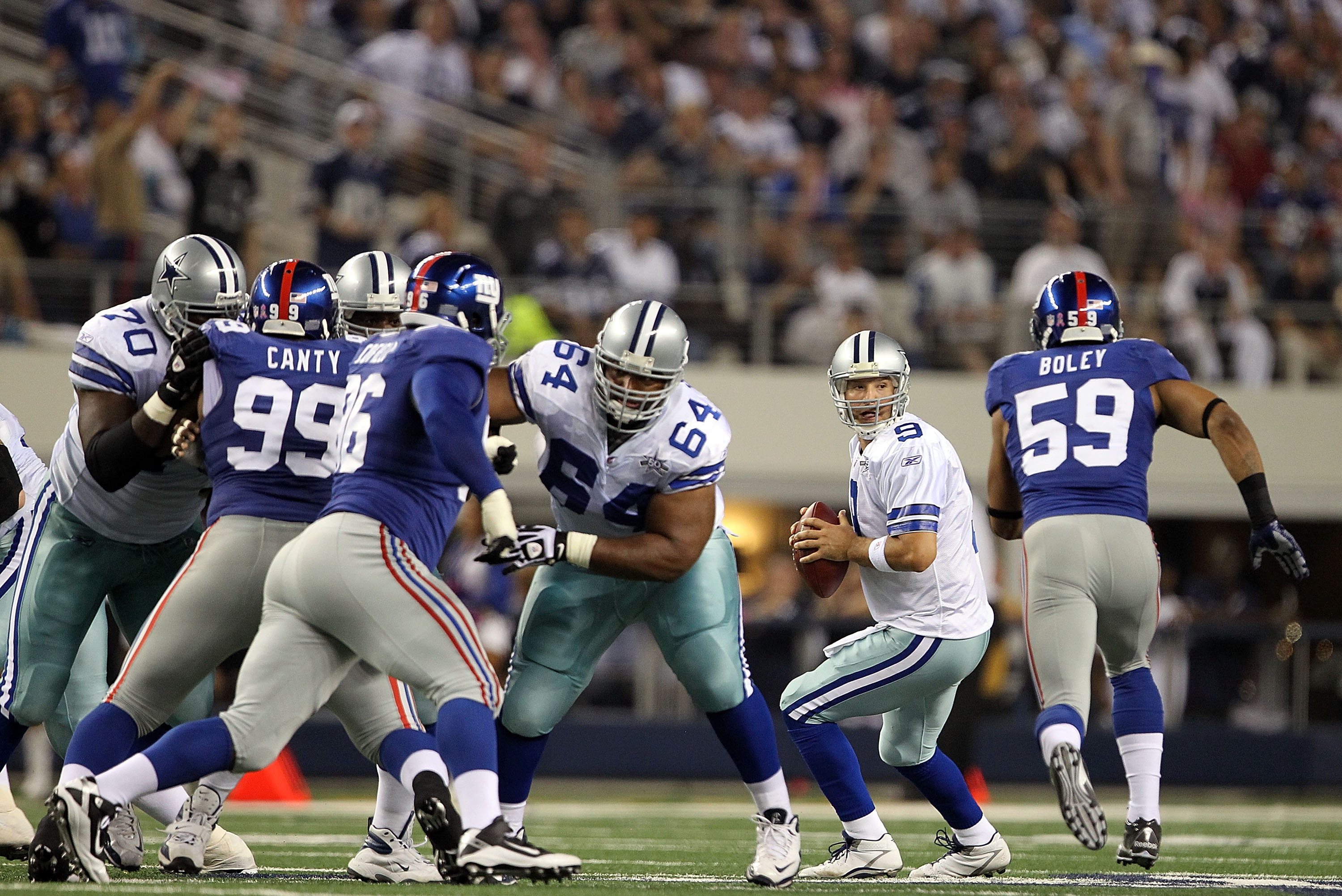 ARLINGTON, TX - OCTOBER 25:  Quarterback Tony Romo #9 of the Dallas Cowboys drops back to pass before a hit by Michael Boley #59 of the New York Giants in the second quarter at Cowboys Stadium on October 25, 2010 in Arlington, Texas.  Romo did not return