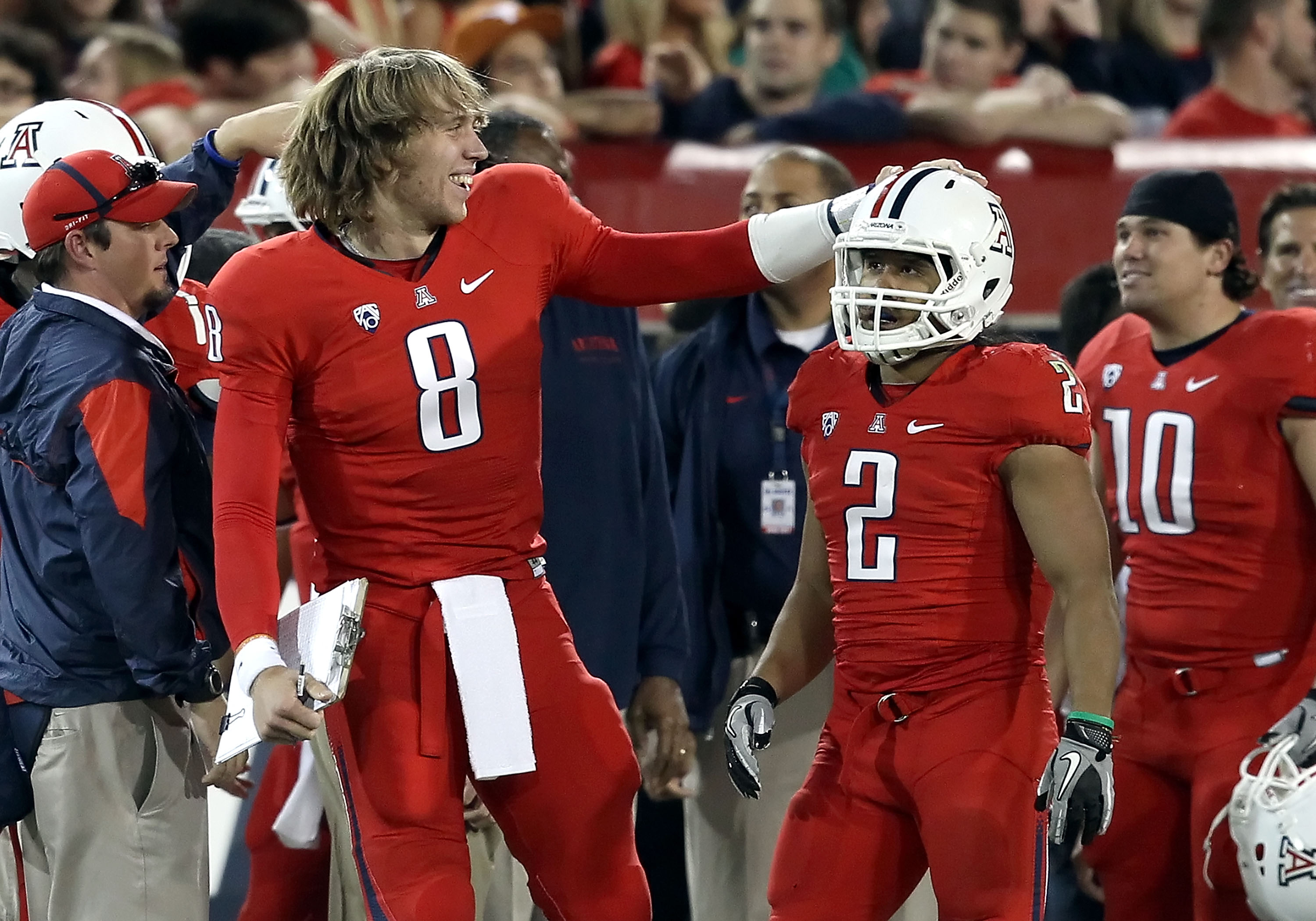 TUCSON, AZ - OCTOBER 23:  Injured quarterback Nick Foles #8 of the Arizona Wildcats congratulates Keola Antolin #2 after Antolin scored a 78 yard rushing touchdown against the Washington Huskies during the second quarter of the college football game at Ar
