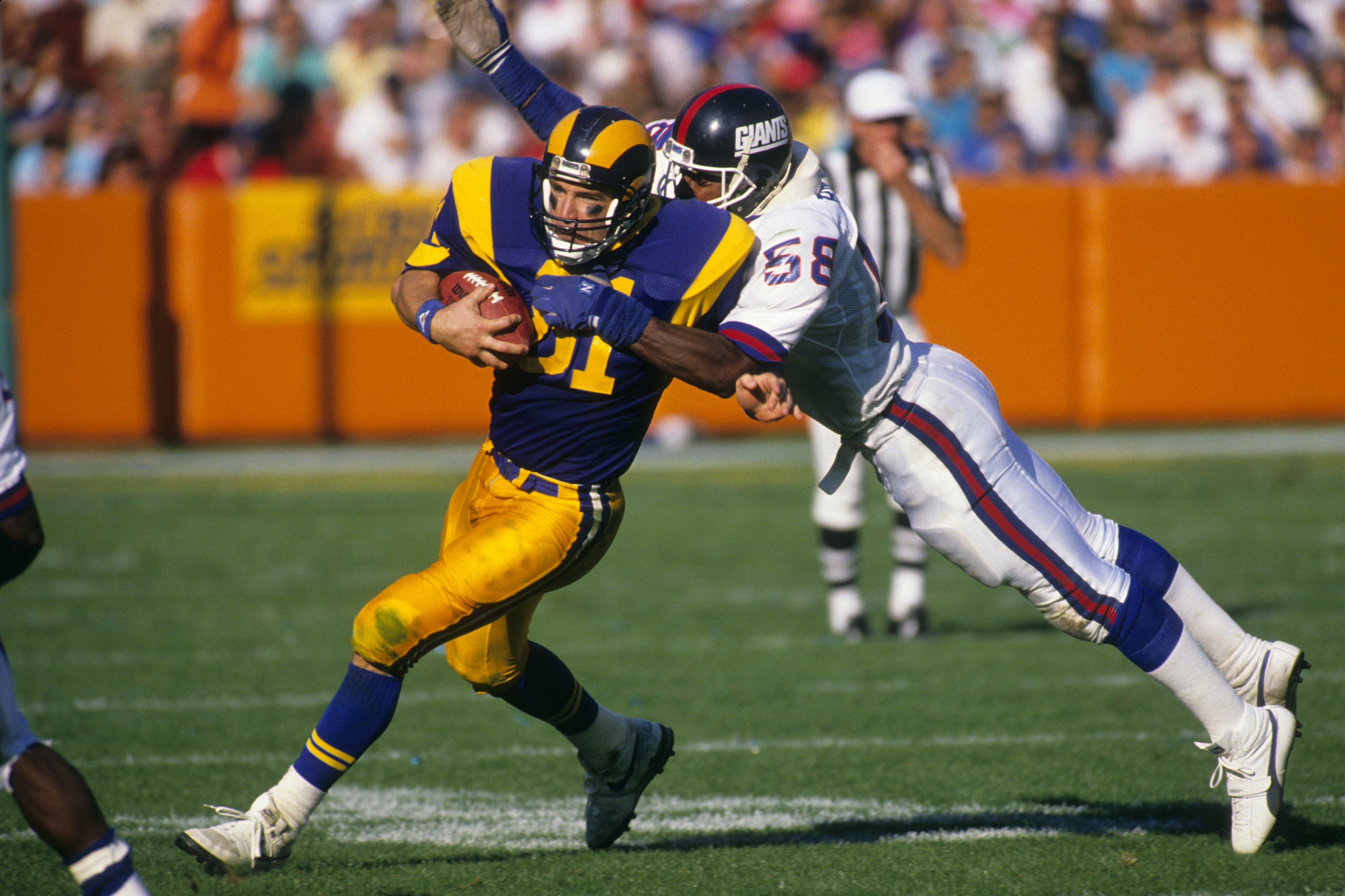ANAHEIM, CA - NOVEMBER 12:  Tight end Pete Holohan #81 of the Los Angeles Rams tries to break a tackle by  linebacker Carl Banks #58 of the New York Giants during the game at Anaheim Stadium on November 12, 1989 in Anaheim, California. The Rams won 31-10.