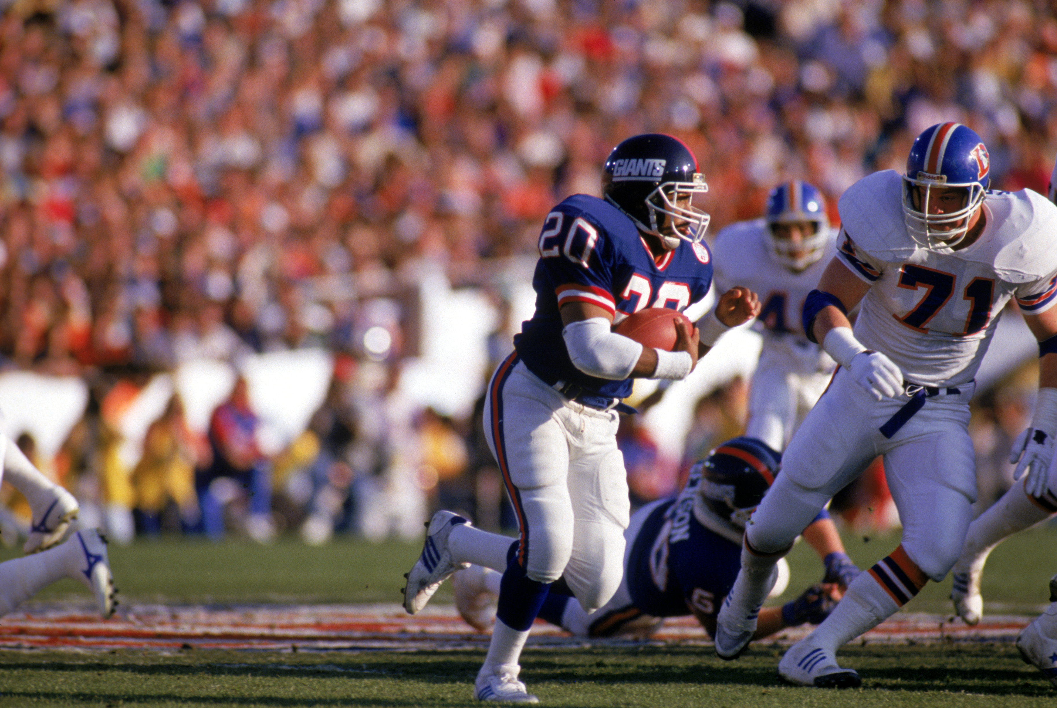PASADENA, CA - JANUARY 25:  Running back Joe Morris #20 of the New York Giants carries the ball against nose tackle Greg Kragen #71 of the Denver Broncos during Super Bowl XXI at the Rose Bowl on January 25, 1987 in Pasadena, California. The Giants defeat