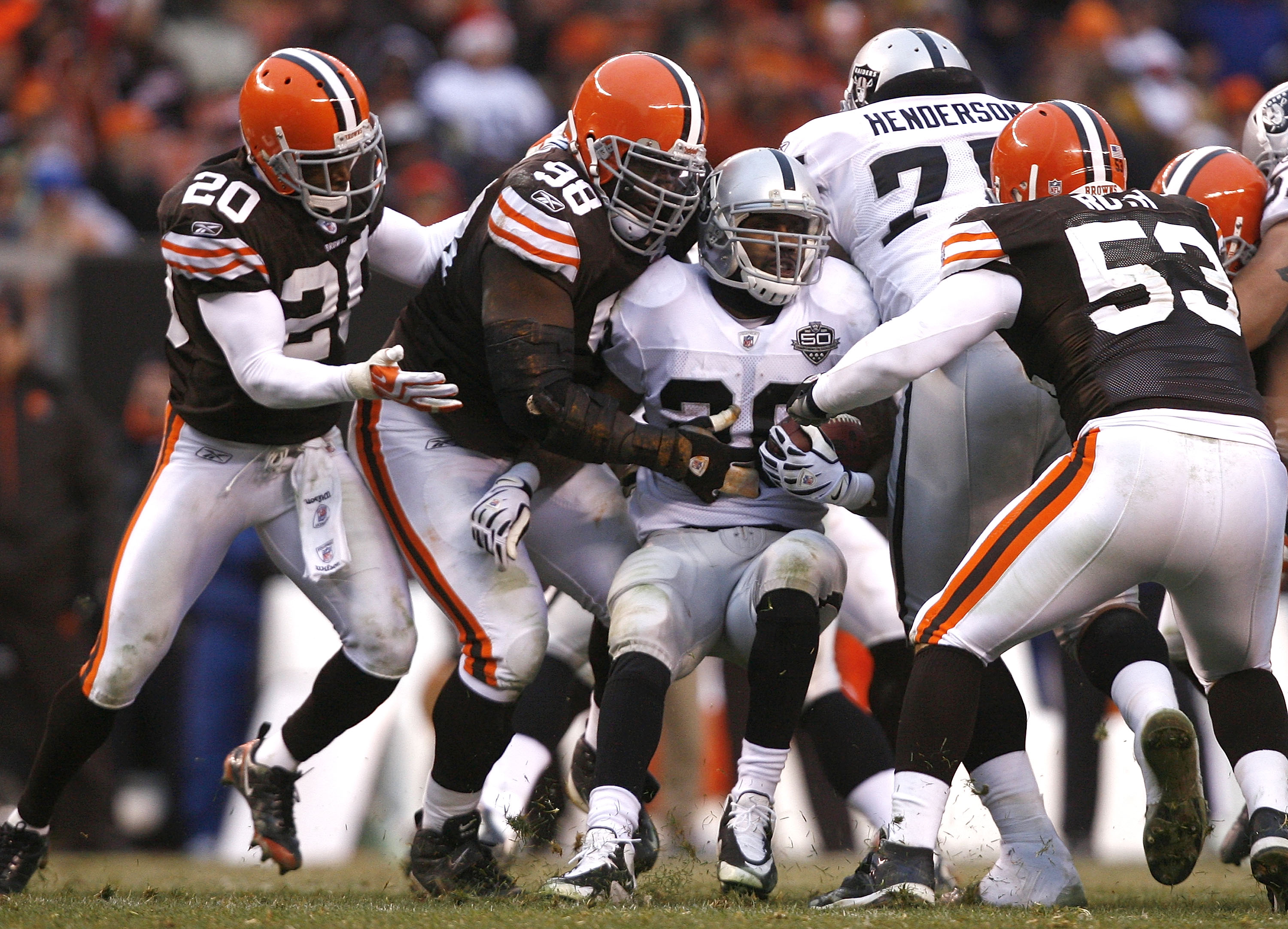 CLEVELAND - DECEMBER 27:  Mike Adams #20, Robaire Smith #98 and Matt Roth #53 of the Cleveland Browns tackle Darren McFadden #20 of the Oakland Raiders at Cleveland Browns Stadium on December 27, 2009 in Cleveland, Ohio.  (Photo by Matt Sullivan/Getty Ima