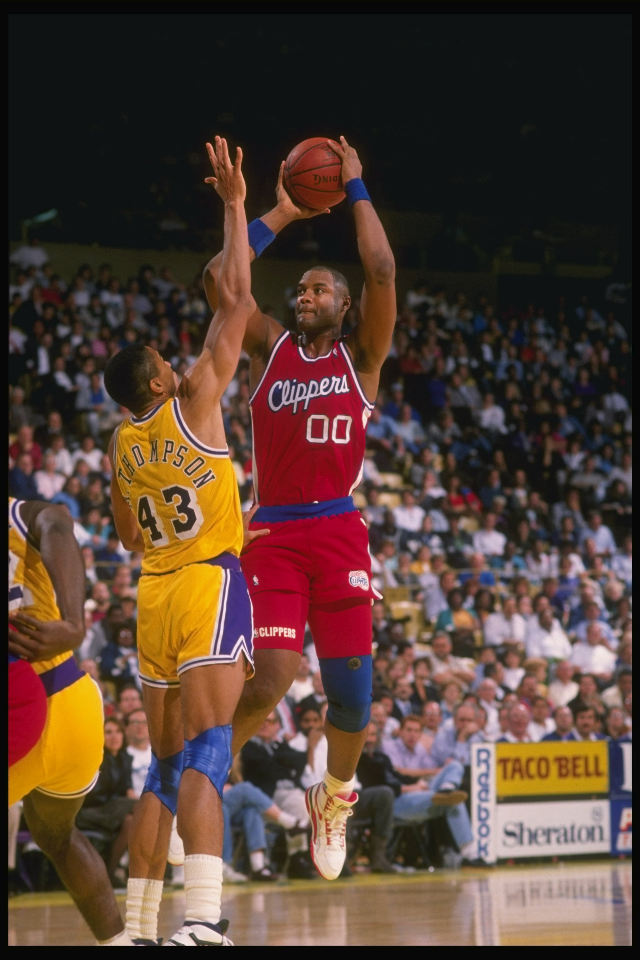 1989-1990:  Center Benoit Benjamin of the Los Angeles Clippers (right) tries to shoot the ball as Mychal Thompson of the Los Angeles Lakers blocks during a game at the Great Western Forum in Inglewood, California. Mandatory Credit: Ken Levine  /Allsport