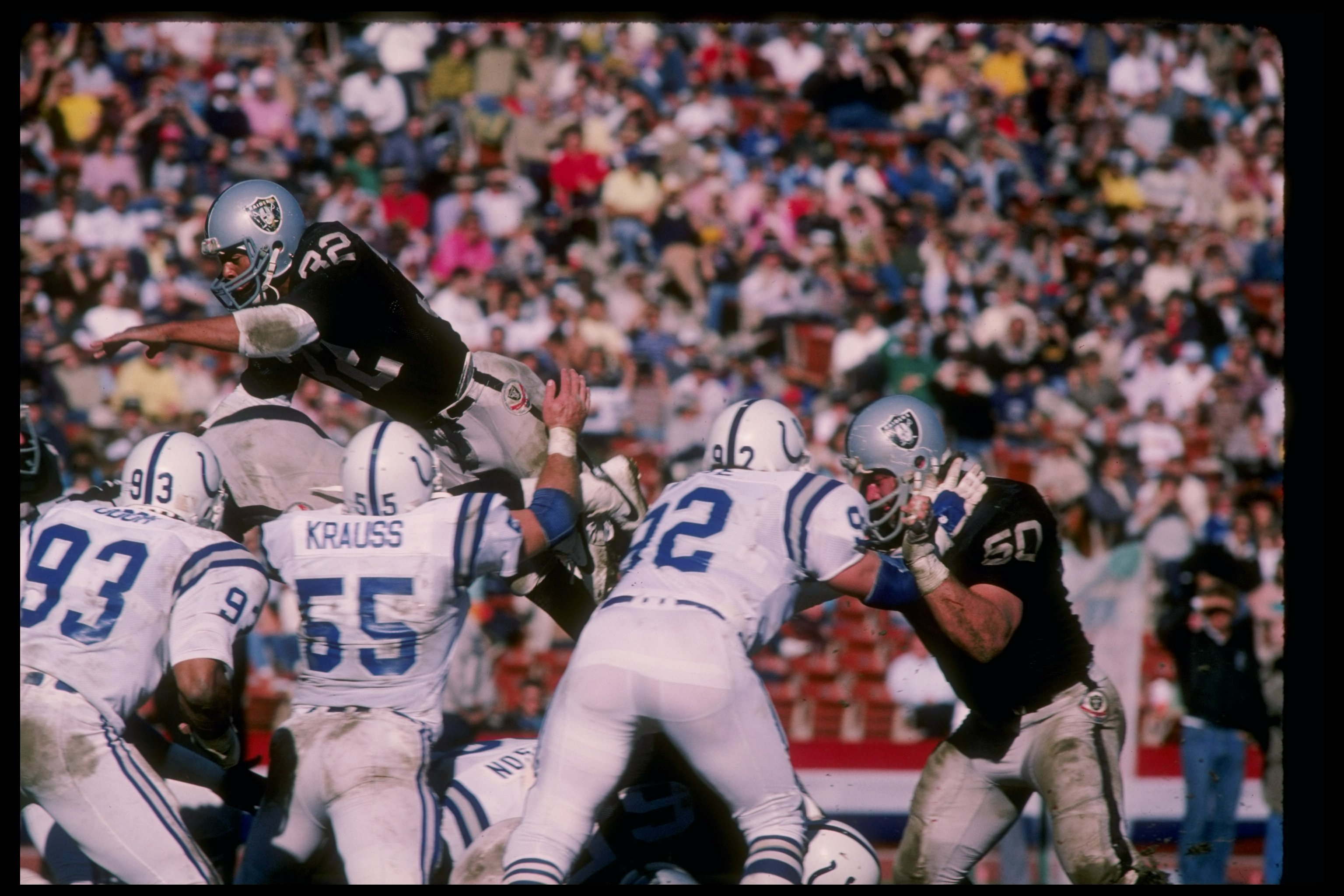 25 Nov 1984:  Running back Marcus Allen of the Los Angeles Raiders (top) sails over for a touchdown during a game against the Indianapolis Colts at the Los Angeles Memorial Coliseum in Los Angeles, California.  The Raiders won the game 21-7. Mandatory Cre