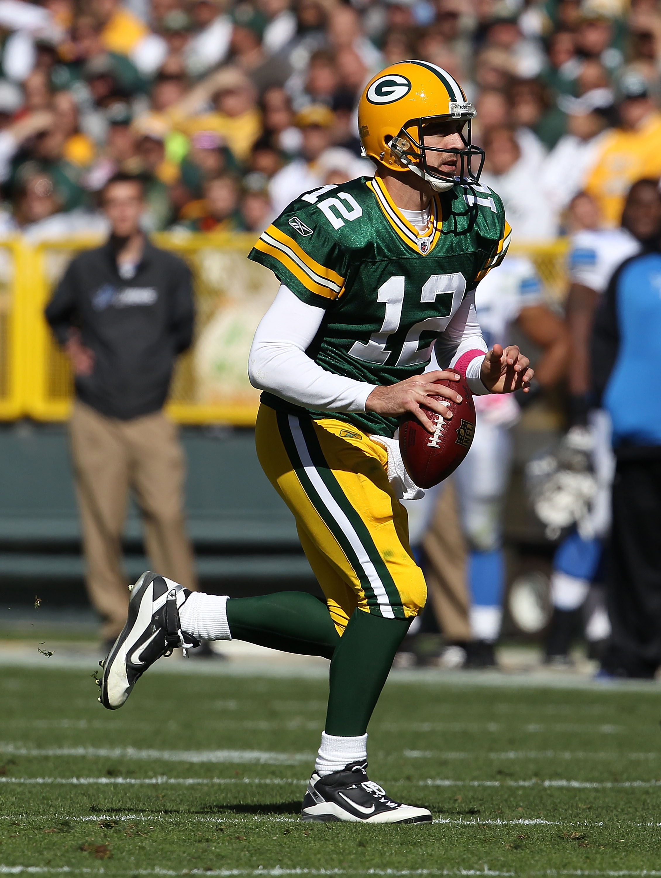 GREEN BAY, WI - OCTOBER 03: Aaron Rodgers #12 of the Green Bay Packers rolls out to look for a receiver against the Detroit Lions at Lambeau Field on October 3, 2010 in Green Bay, Wisconsin. The Packers defeated the Lions 28-26. (Photo by Jonathan Daniel/