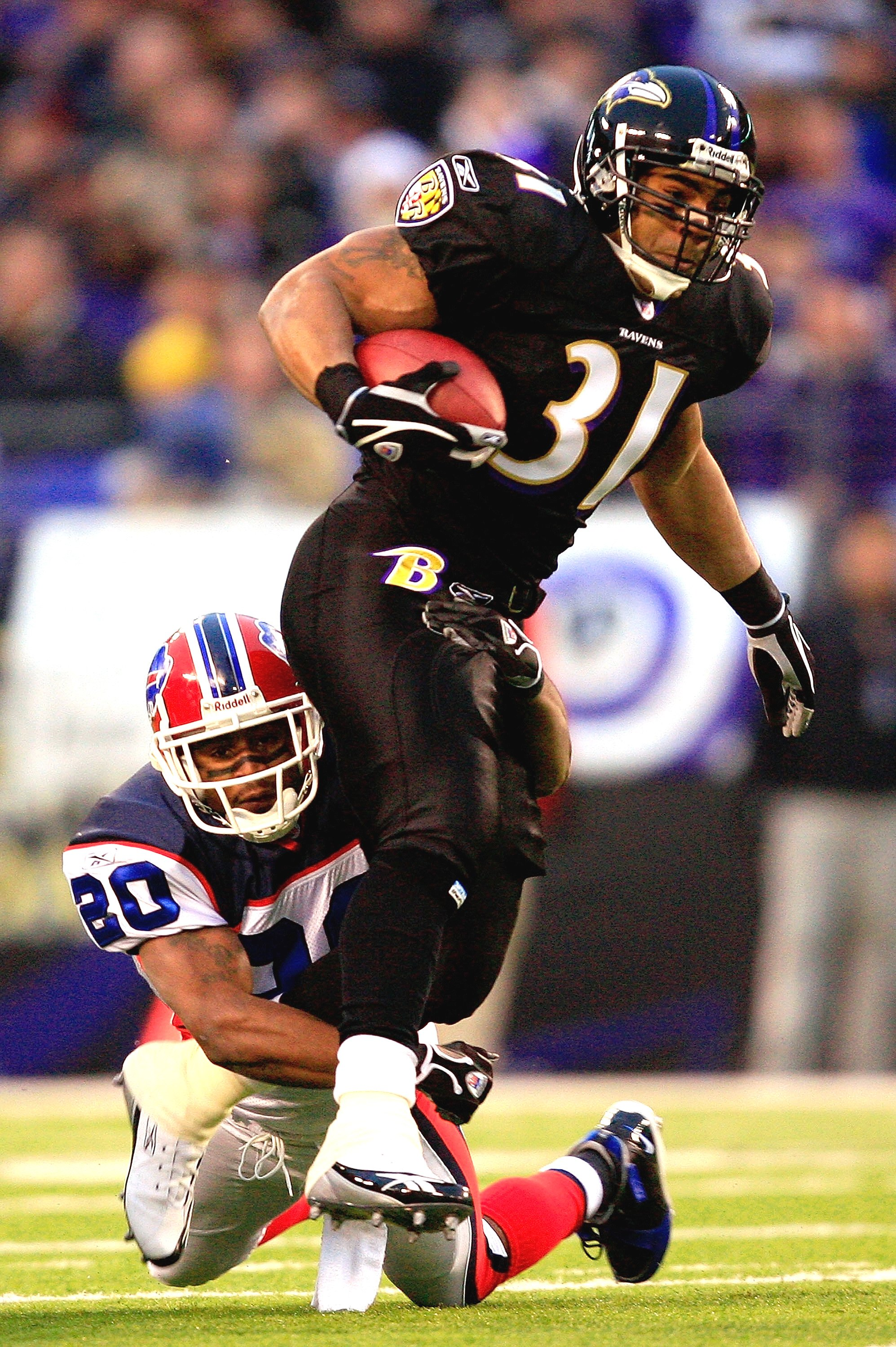 BALTIMORE - DECEMBER 31:  Jamal Lewis #31 of the Baltimore Ravens carries the ball as Donte Whitner #20 of the Buffalo Bills defends during the first half of the game on December 31, 2006 at M&T Bank Stadium in Baltimore, Maryland.  (Photo by Jamie Squire