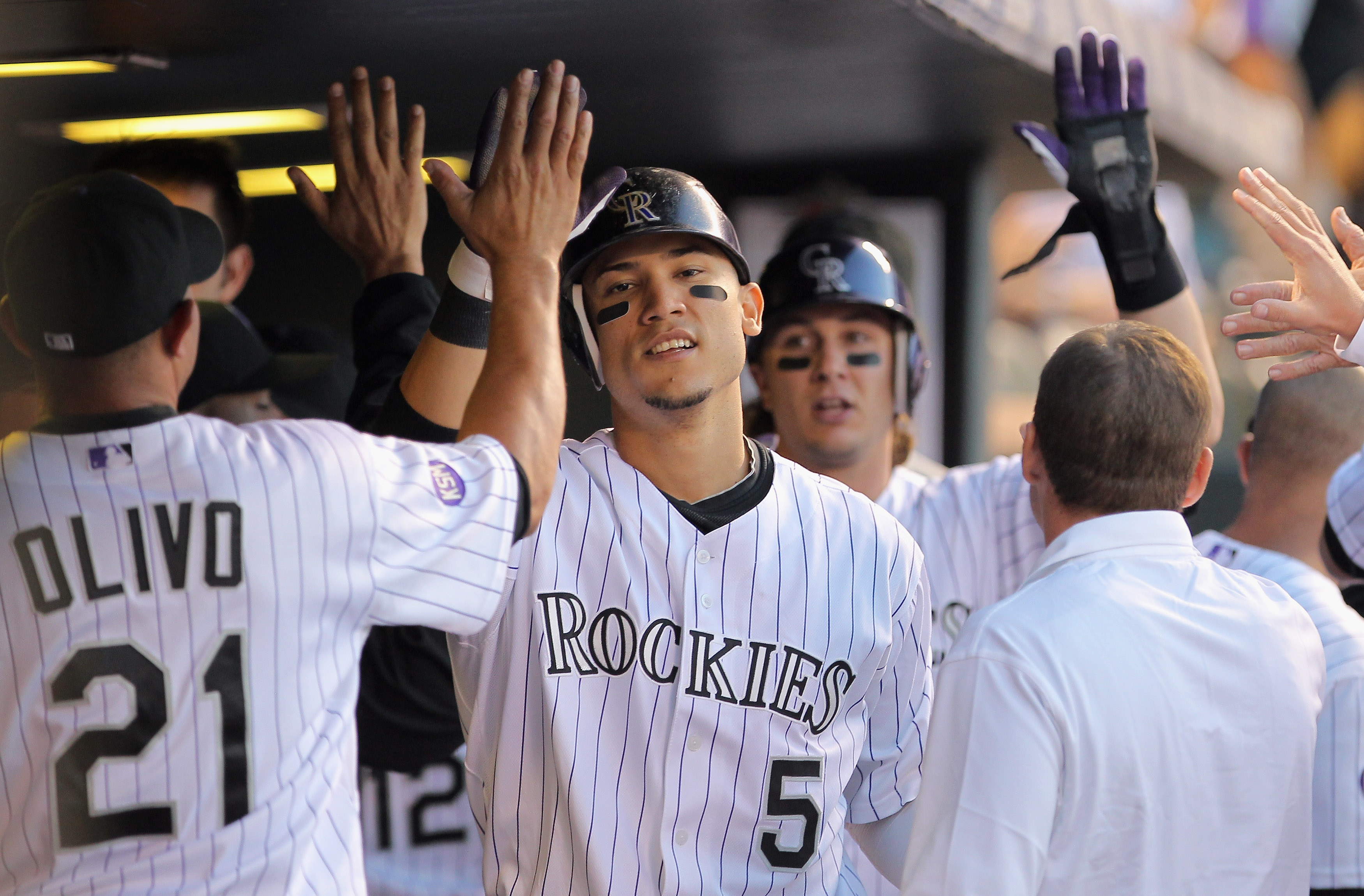 DENVER - SEPTEMBER 25:  Carlos Gonzalez #5 and Troy Tulowitzki #2 of the Colorado Rockies celebrate in the dugout after scoring on a Melvin Mora single to give the Rockies a 2-1 lead over the San Francisco Giants in the first inning at Coors Field on Sept