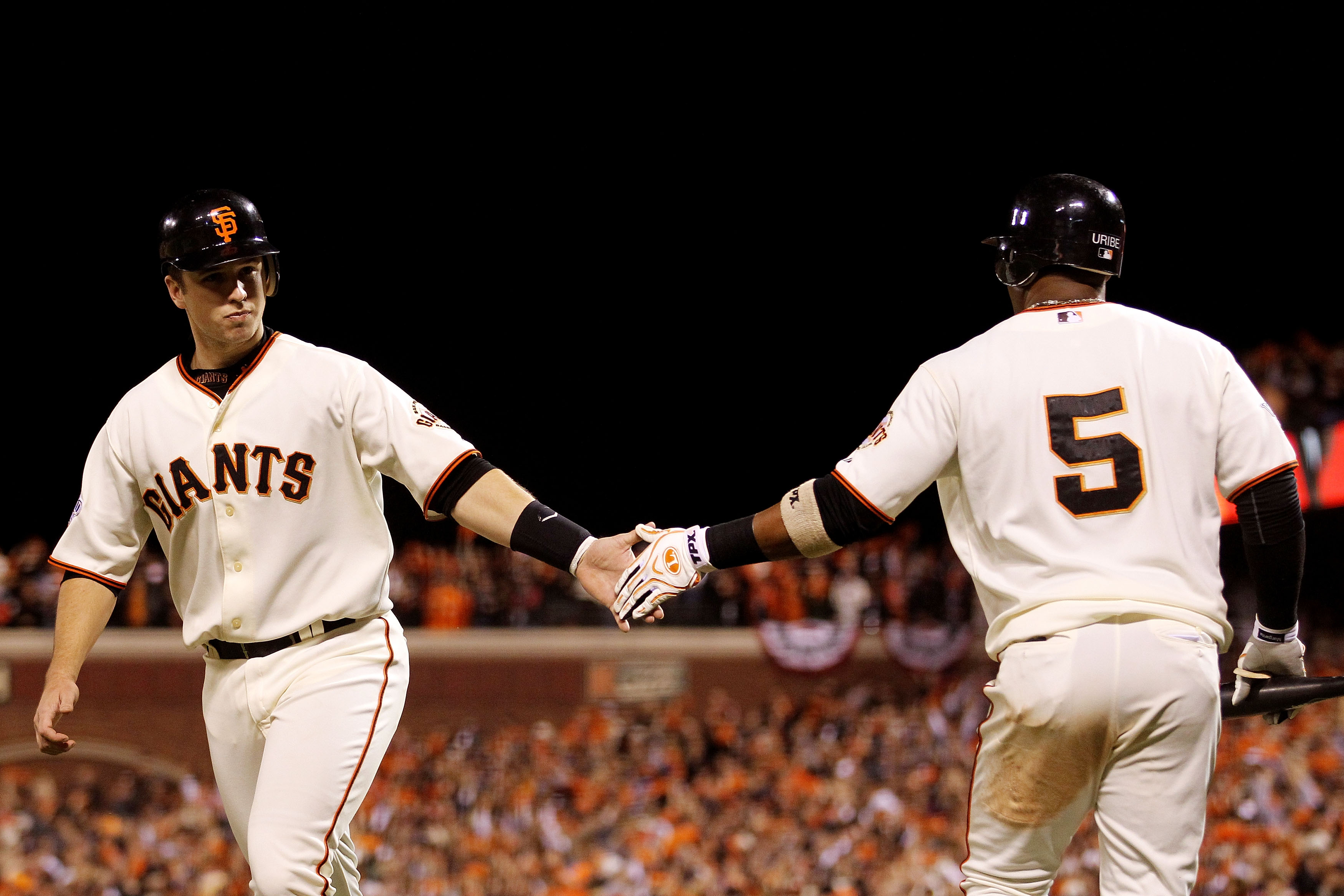 SAN FRANCISCO - OCTOBER 28:  Buster Posey #28 of the San Francisco Giants celebrates scoring a run with teammate Juan Uribe #5 in the eighth inning while taking on the Texas Rangers in Game Two of the 2010 MLB World Series at AT&T Park on October 28, 2010
