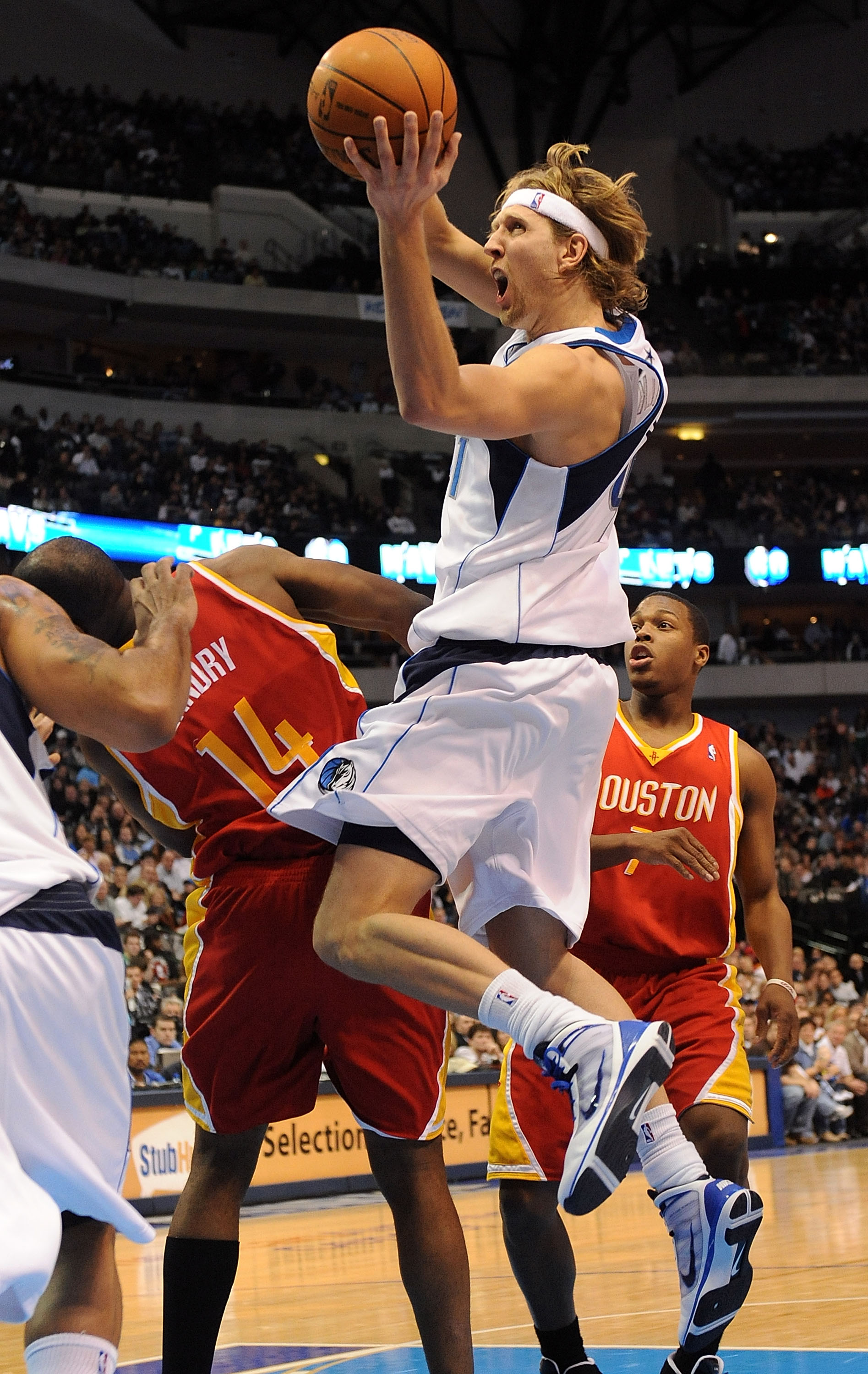 DALLAS - DECEMBER 18:  Forward Dirk Nowitzki #41 of the Dallas Mavericks takes a shot against Carl Landry #14 of the Houston Rockets on December 18, 2009 at American Airlines Center in Dallas, Texas.  NOTE TO USER: User expressly acknowledges and agrees t