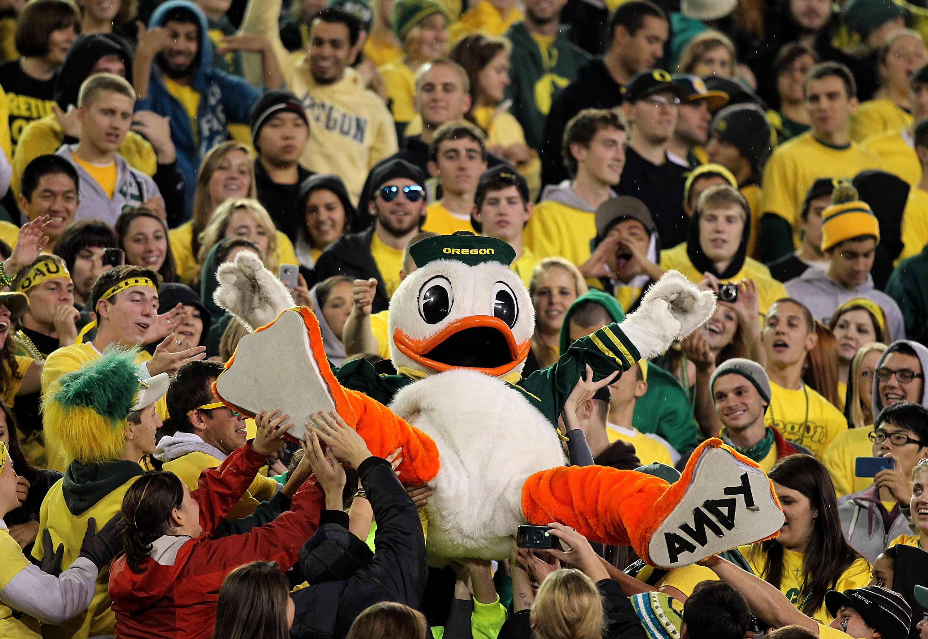 EUGENE, OR - OCTOBER 21:  The Oregon Duck mascot is lifted into the crowd during the game against the UCLA Bruins  on October 21, 2010 at the Autzen Stadium in Eugene, Oregon.  (Photo by Jonathan Ferrey/Getty Images)