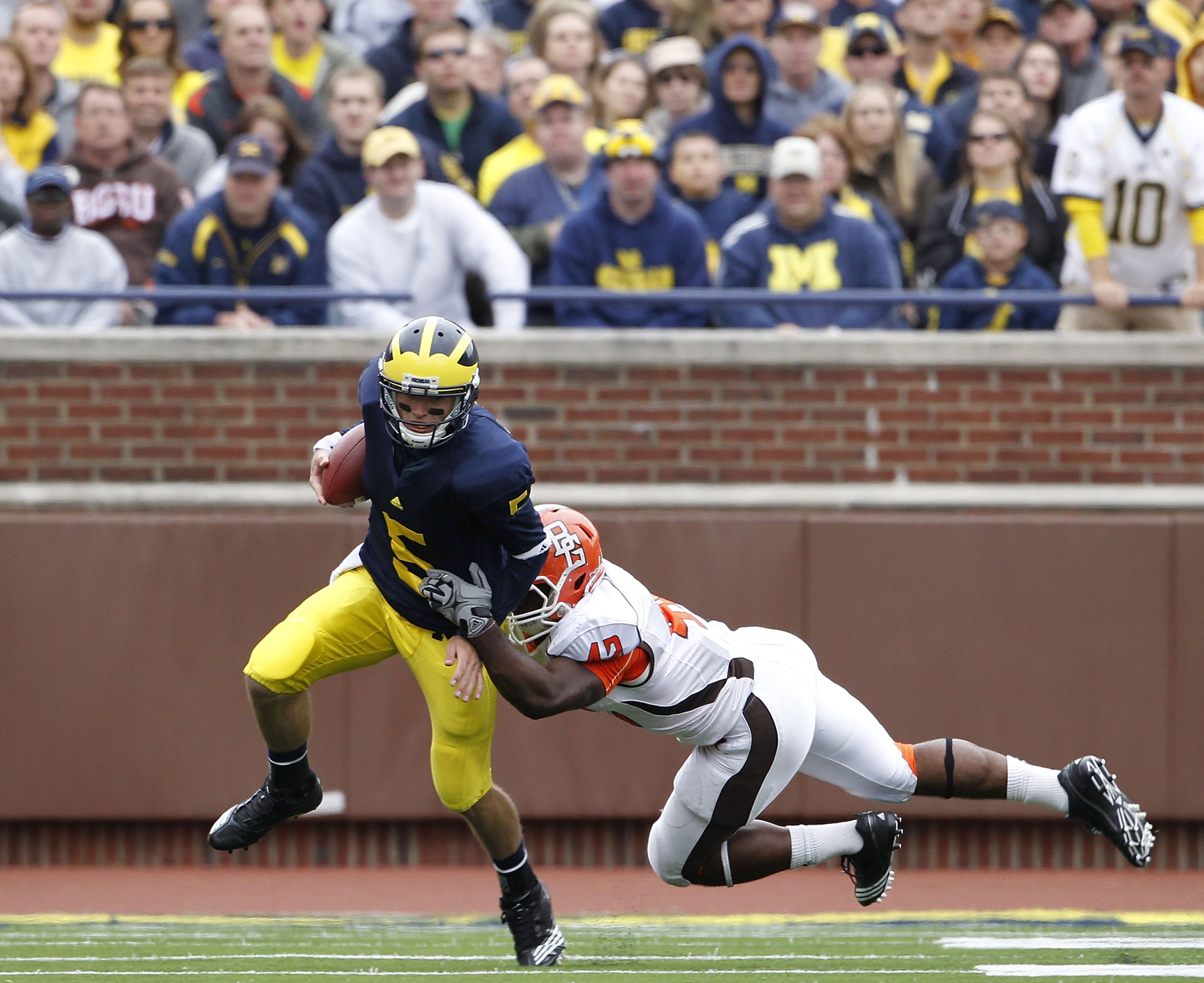 ANN ARBOR, MI - SEPTEMBER 25: Tate Forcier #5 of the Michigan Wolverines runs for a short gain as Eugene Fells #42 of Bowling Green makes the stop on September 25, 2010 at Michigan Stadium in Ann Arbor, Michigan. Michigan defeated Bowling Green 65-21.  (P